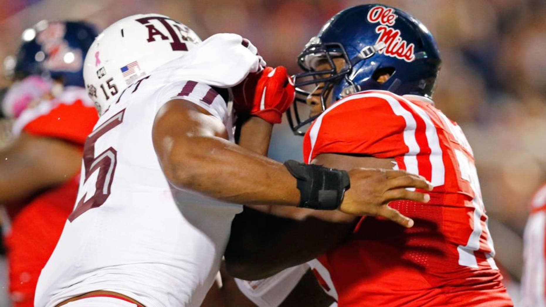Texas A&M defensive lineman Myles Garrett (15) is locked up by Mississippi offensive lineman Laremy Tunsil (78) during the first half of an NCAA college football game in Oxford, Miss., Saturday, Oct. 24, 2015. (AP Photo/Rogelio V. Solis)