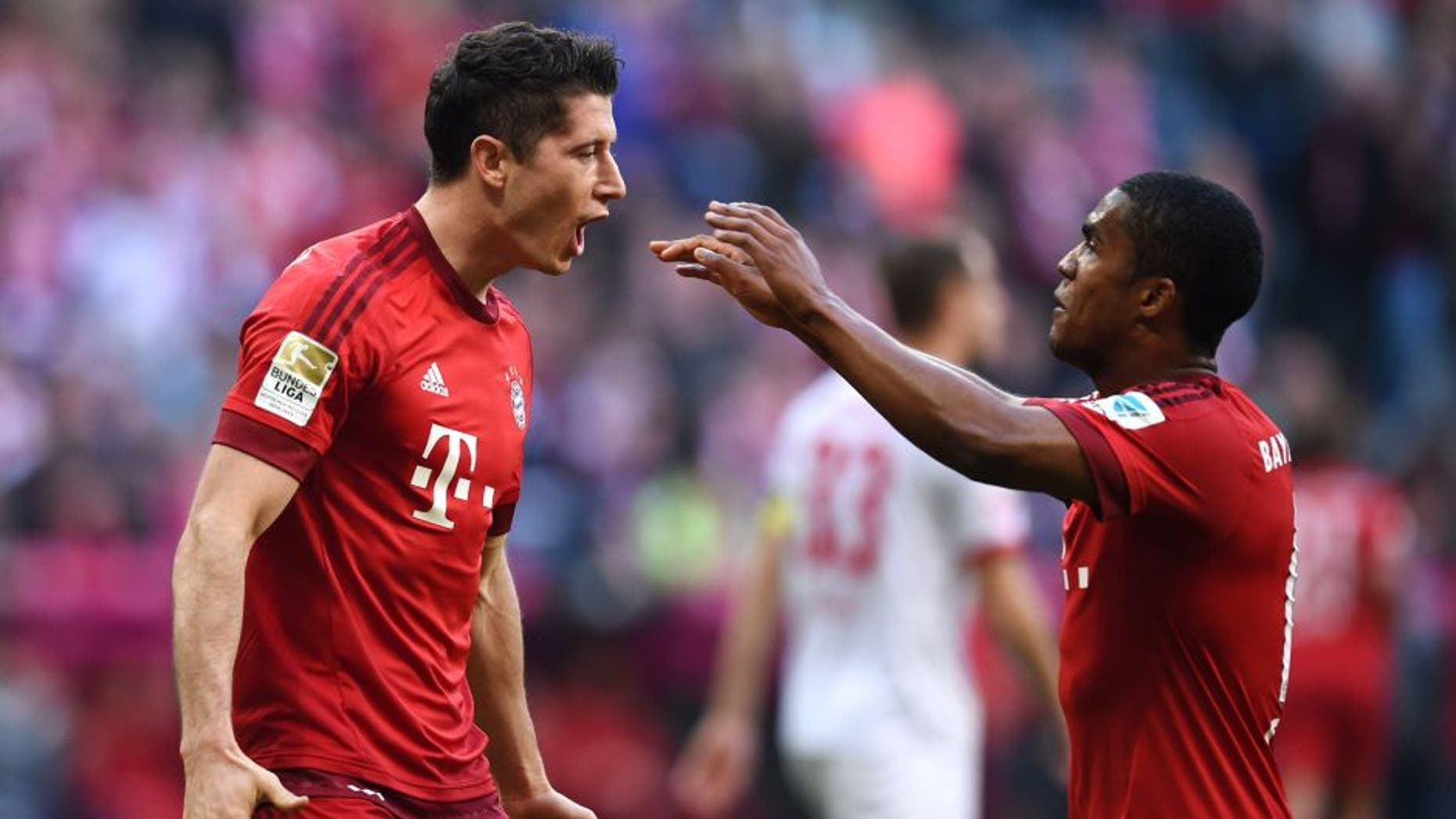 MUNICH, GERMANY - OCTOBER 24: Robert Lewandowski of Muenchen celebrates with his team-mates after scoring his team's third goal during the Bundesliga match between FC Bayern Muenchen and 1. FC Koeln at Allianz Arena on October 24, 2015 in Munich, Germany. (Photo by Matthias Hangst/Bongarts/Getty Images)