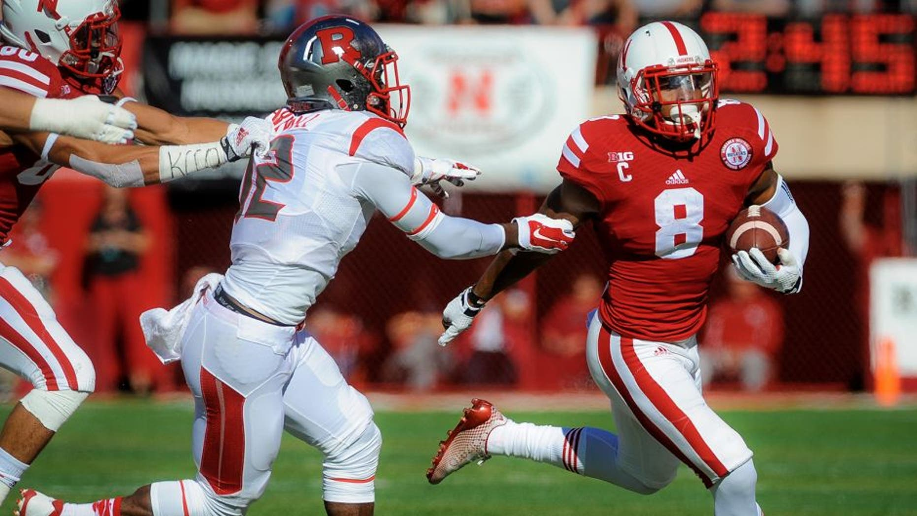 LINCOLN, NE - OCTOBER 25: Running back Ameer Abdullah #8 of the Nebraska Cornhuskers runs past defensive back Nadir Barnwell #12 of the Rutgers Scarlet Knights during their game at Memorial Stadium on October 25, 2014 in Lincoln, Nebraska. (Photo by Eric Francis/Getty Images)
