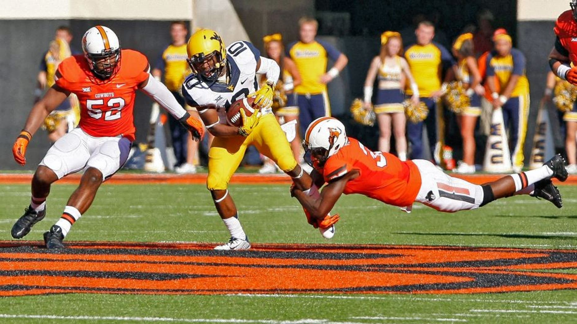 Oct 25, 2014; Stillwater, OK, USA; West Virginia Mountaineers wide receiver Jordan Thompson (center) is tackled by Oklahoma State Cowboys linebacker Ryan Simmons (left) and safety Tre Flowers (right) during the second quarter at Boone Pickens Stadium. Mandatory Credit: Alonzo Adams-USA TODAY Sports
