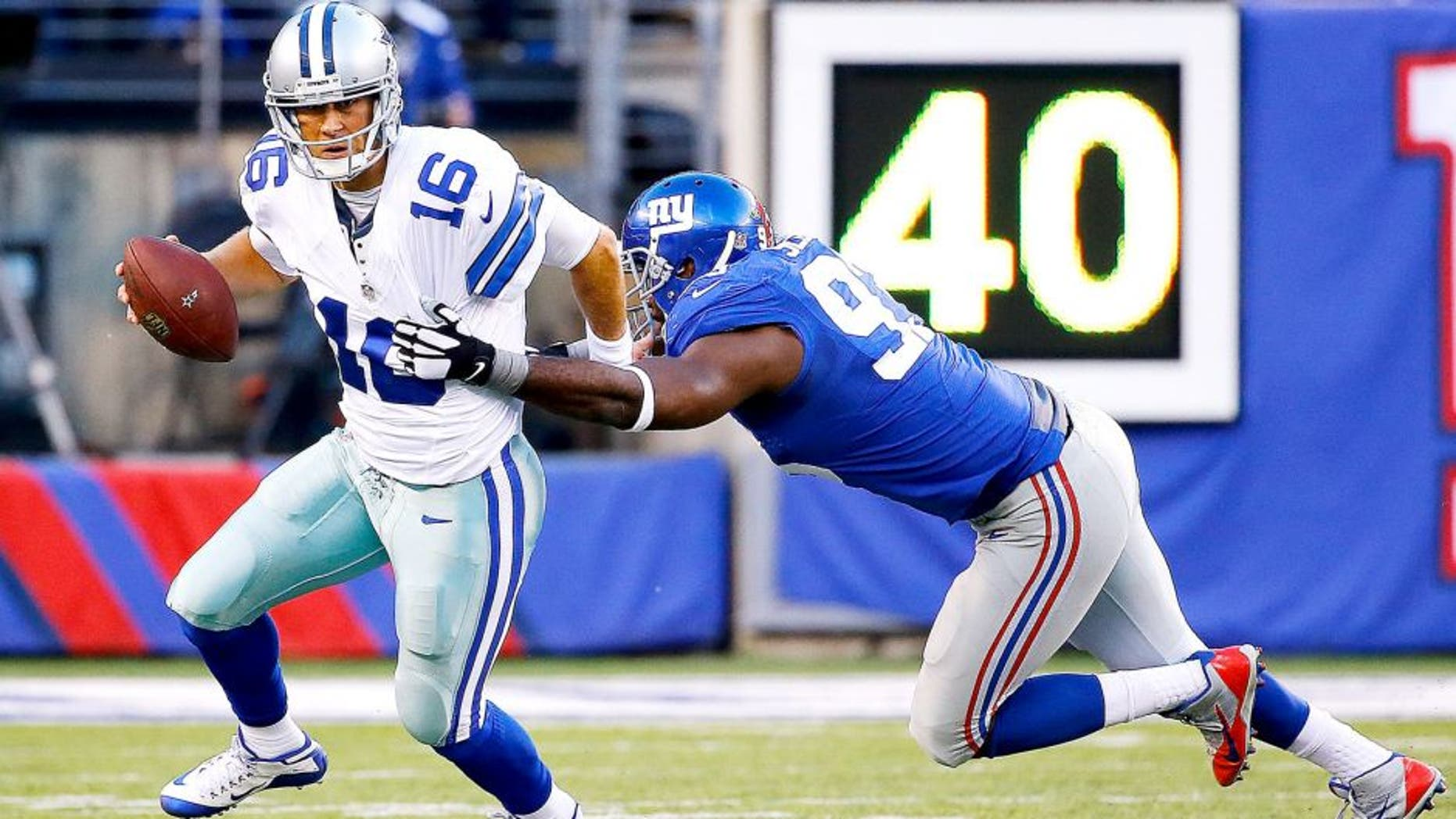 EAST RUTHERFORD, NJ - OCTOBER 25: Matt Cassel #16 of the Dallas Cowboys escapes the tackle attempt by George Selvie #93 of the New York Giants during the second quarter at MetLife Stadium on October 25, 2015 in East Rutherford, New Jersey. (Photo by Al Bello/Getty Images)