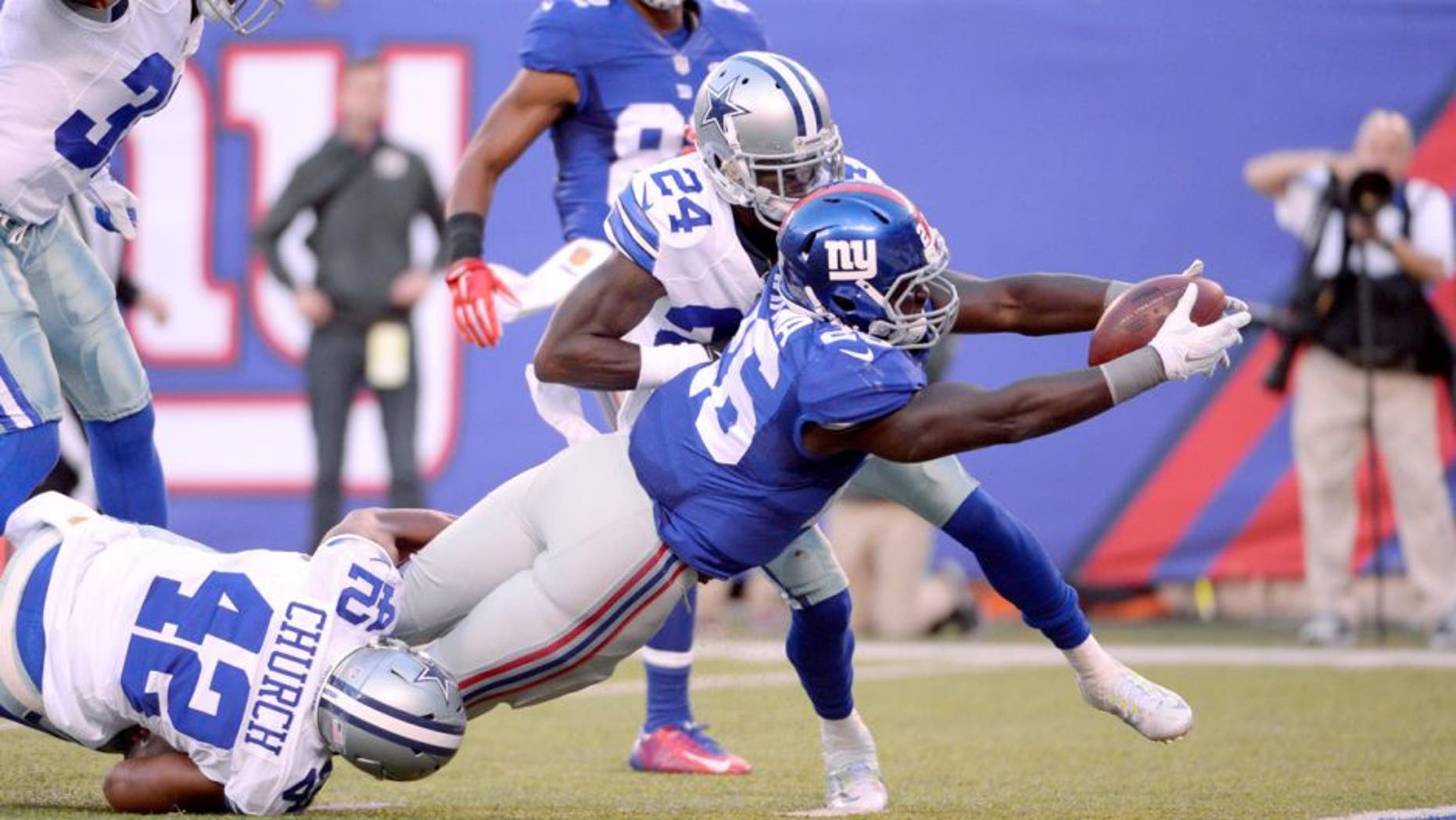 Oct 25, 2015; East Rutherford, NJ, USA; New York Giants running back Orleans Darkwa (26) dives for a touchdown pas Dallas Cowboys strong safety Barry Church (42) in the first half during the NFL game at MetLife Stadium. Mandatory Credit: Robert Deutsch-USA TODAY Sports