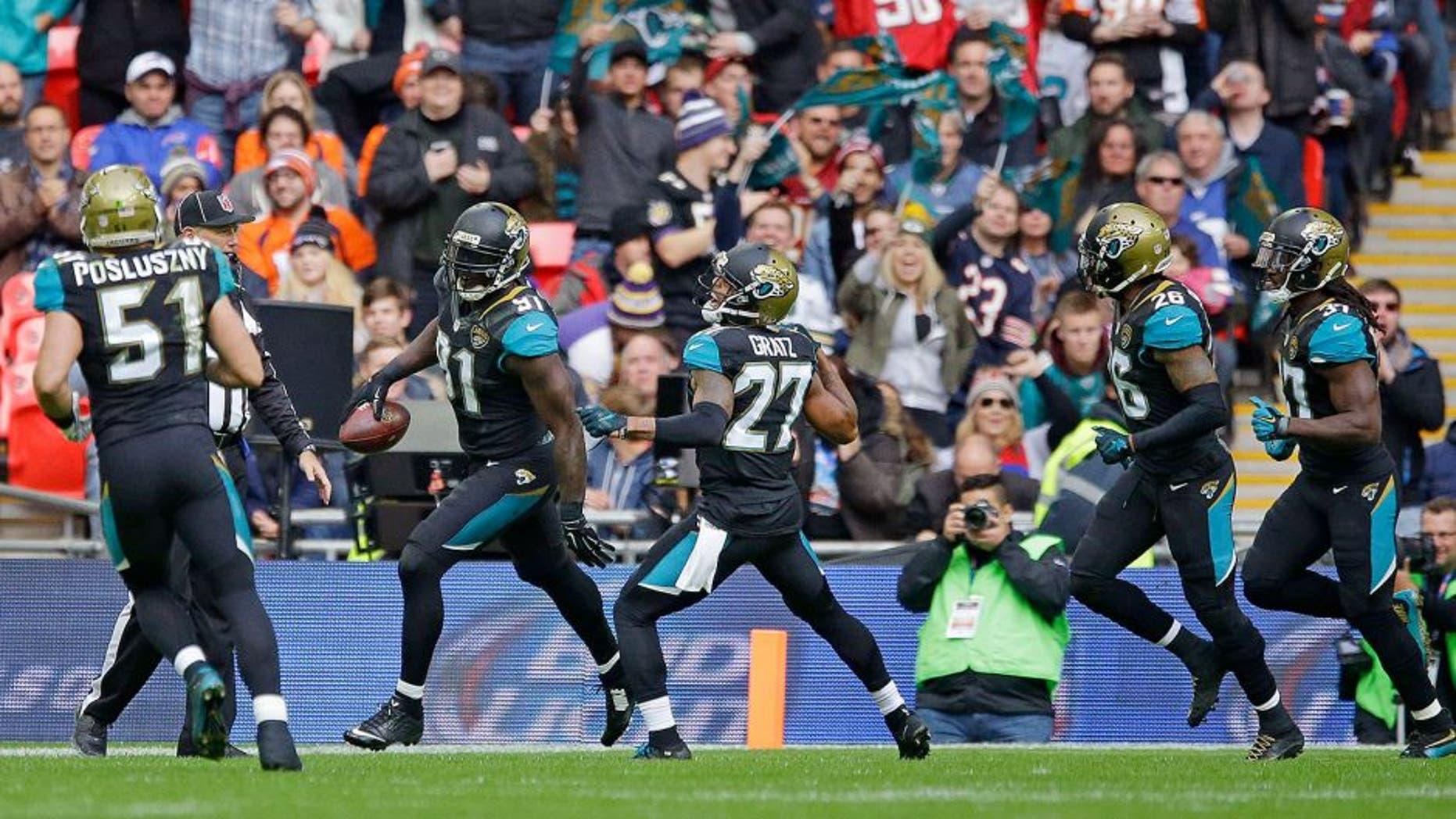 Jacksonville Jaguars defensive end Chris Clemons (91), second left reacts after scoring a touchdown during the NFL game between Buffalo Bills and Jacksonville Jaguars at Wembley Stadium in London, Sunday, Oct. 25, 2015. (AP Photo/Matt Dunham)