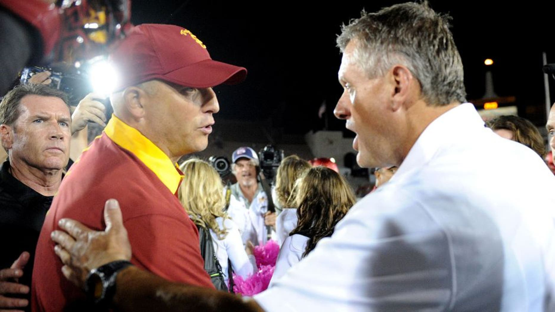 October 24, 2015; Los Angeles, CA, USA; Southern California Trojans interim head coach Clay Helton meets with Utah Utes head coach Kyle Whittingham following the 42-24 victory at Los Angeles Memorial Coliseum. Mandatory Credit: Gary A. Vasquez-USA TODAY Sports
