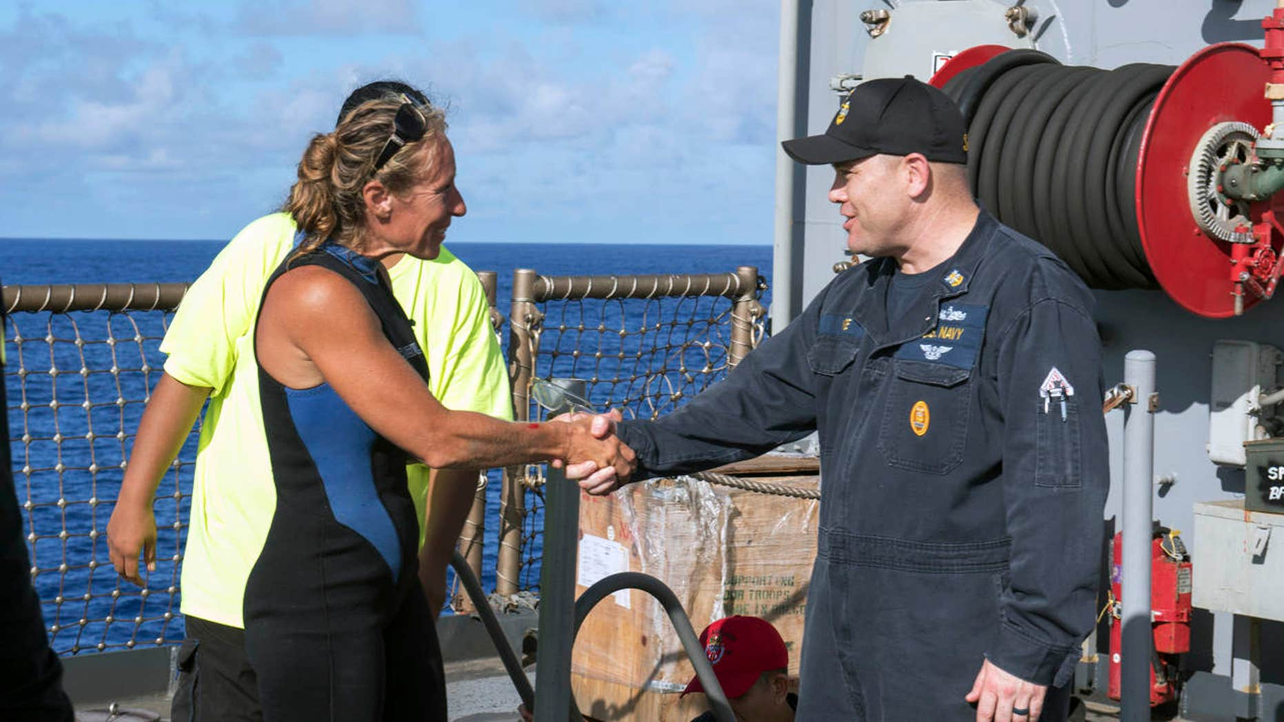 In this Wednesday, Oct. 25, 2017 photo, USS Ashland Command Master Chief Gary Wise welcomes aboard Jennifer Appel, an American mariner, one of two Honolulu women and their dogs who were rescued after being lost at sea for several months while trying to sail from Hawaii to Tahiti.