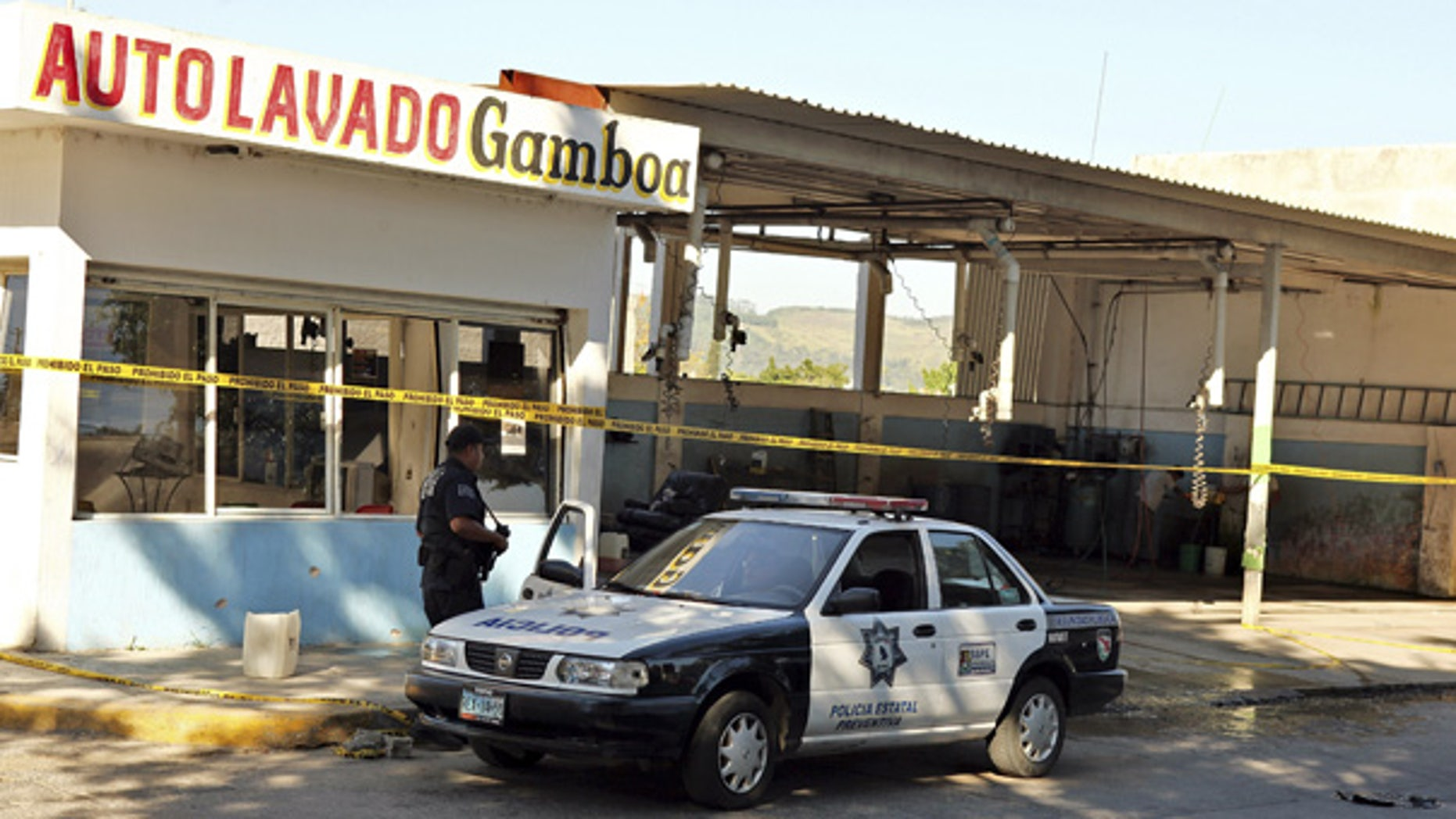 Oct. 27: A police officer is seen outside a car wash after gunmen burst into the shop and killed at least 15 people in Tepic, Mexico.