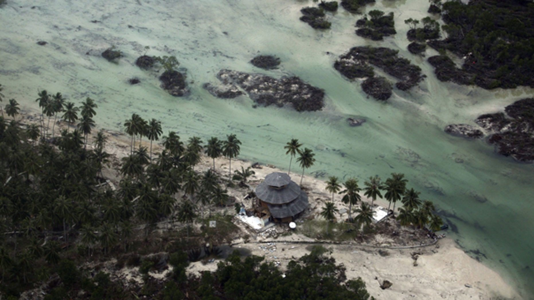 Oct. 27: This aerial photo shows a damaged building in a village flattened by Monday's earthquake triggered tsunami on Pagai island, West Sumatra, Indonesia.