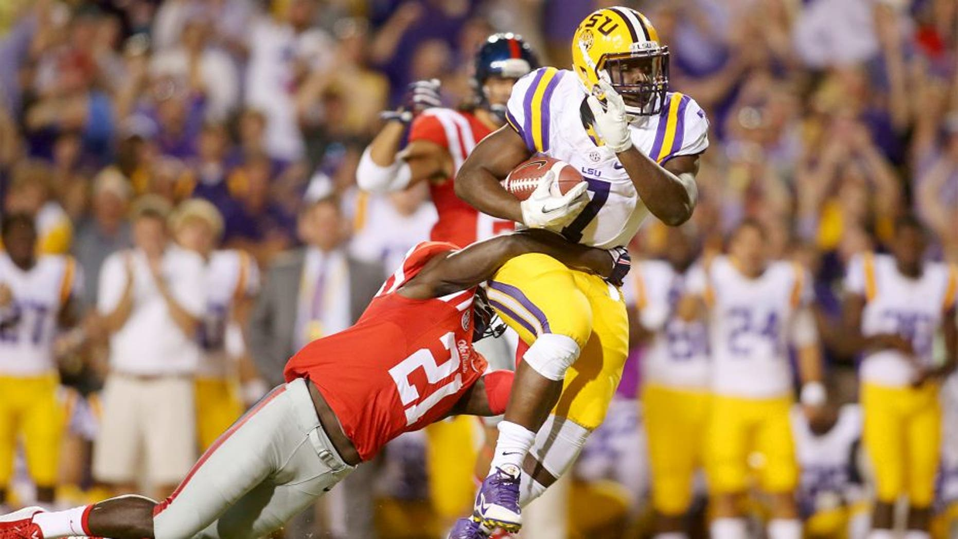 Oct 25, 2014; Baton Rouge, LA, USA; LSU Tigers running back Leonard Fournette (7) is tackled by Mississippi Rebels defensive back Senquez Golson (21) as he carries the ball in the first quarter at Tiger Stadium. Mandatory Credit: Crystal LoGiudice-USA TODAY Sports