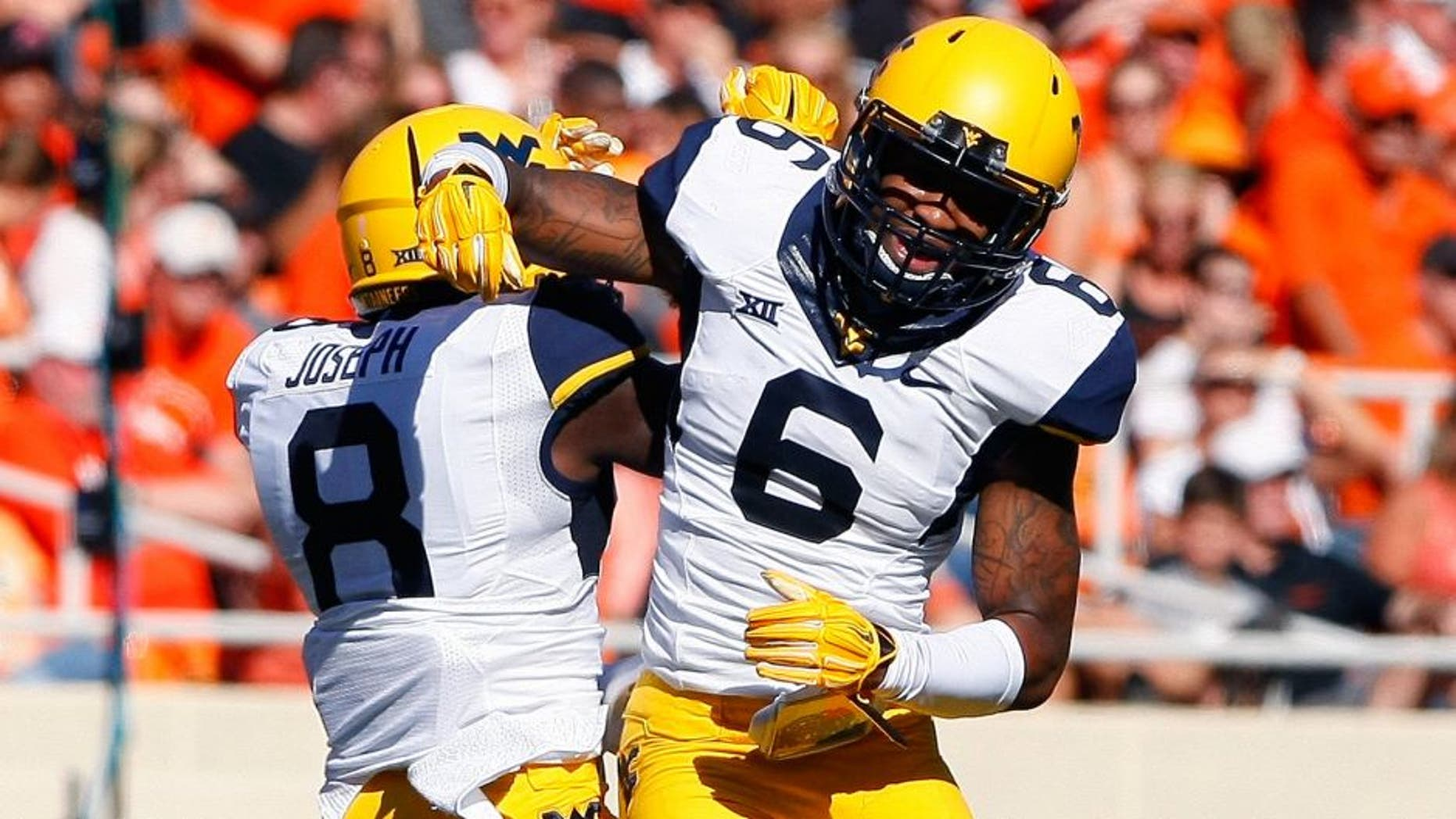 Oct 25, 2014; Stillwater, OK, USA; West Virginia Mountaineers safety Dravon Henry (6) and safety Karl Joseph (8) celebrate after Dravon Henry intercepted an Oklahoma State Cowboy pass during the first quarter at Boone Pickens Stadium. Mandatory Credit: Alonzo Adams-USA TODAY Sports