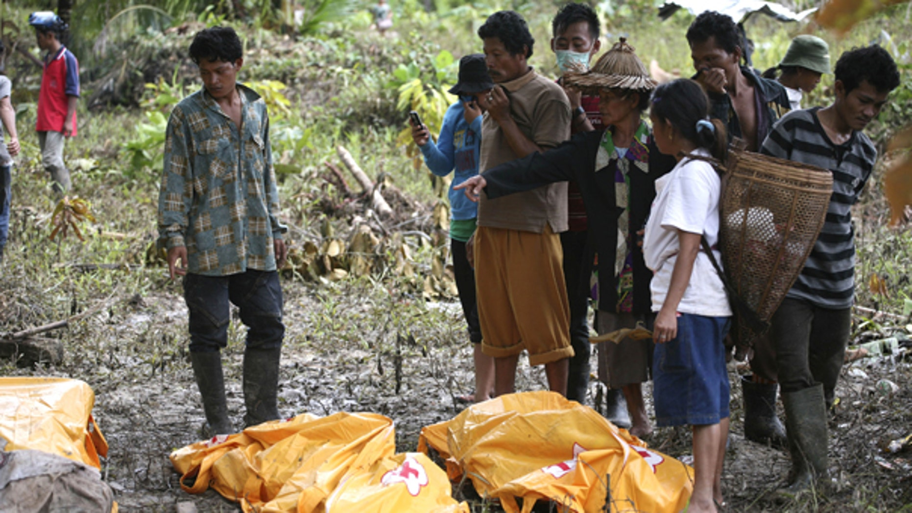 Oct. 29: Survivors look at the body of their family member who died in a tsunami at Munte, Indonesia. he toll from Monday's tsunami rose to more than 400 on Friday as officials found more bodies, and about 300 people were still missing, according to a provincial disaster management center official.