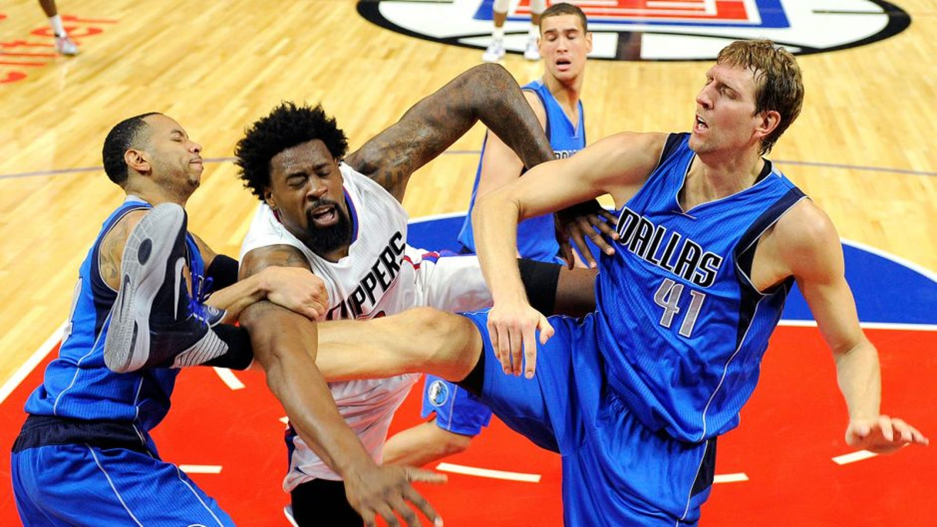LOS ANGELES CA - OCTOBER 29: DeAndre Jordan #6 of the Los Angeles Clippers is fouled by Dirk Nowitzki #41 and Devin Harris of the Dallas Mavericks during the second quarter of the basketball game Staples Center October 29, 2015, in Los Angeles California. (Photo by Kevork Djansezian/Getty Images)