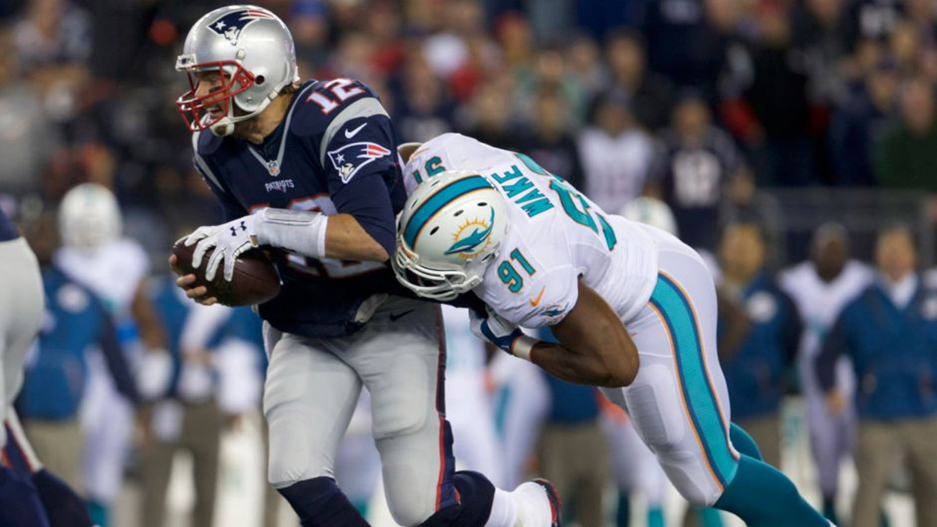 Oct 29, 2015; Foxborough, MA, USA; New England Patriots quarterback Tom Brady (12) is sacked by Miami Dolphins defensive end Cameron Wake (91) in the second quarter at Gillette Stadium. Mandatory Credit: David Butler II-USA TODAY Sports