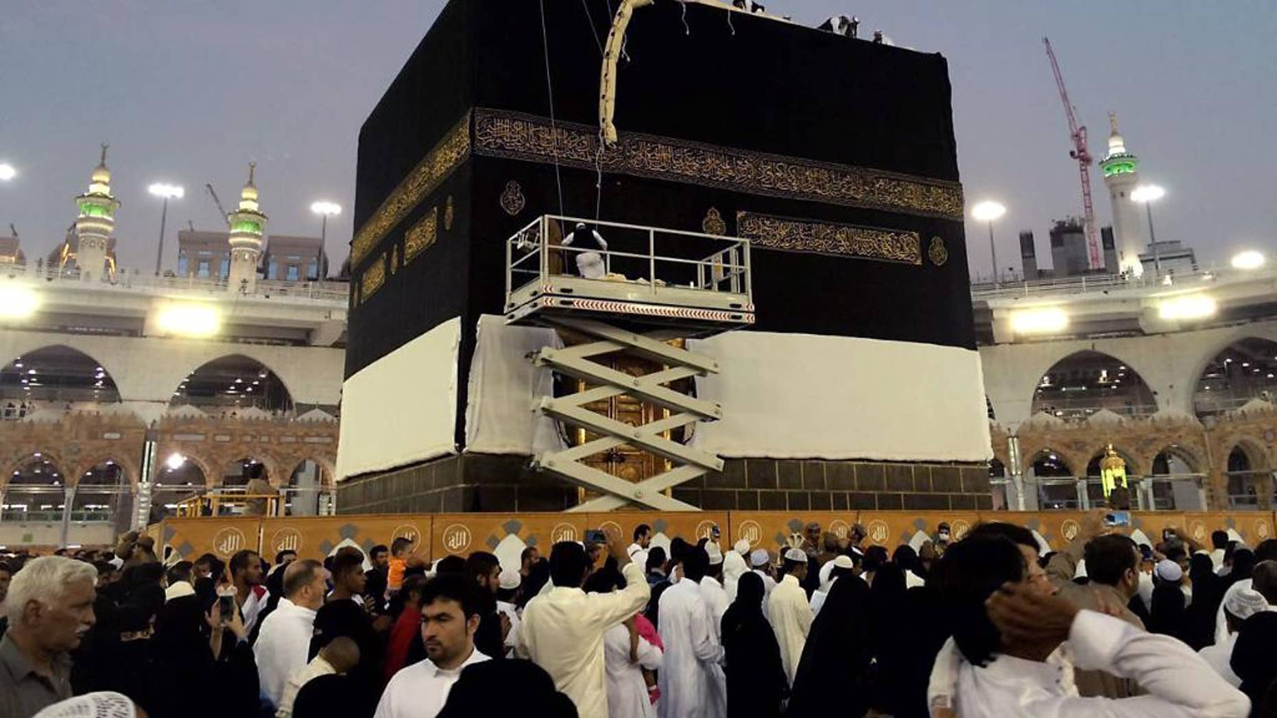 Saudi workers change the Kiswah (the cloth that covers the Kaaba) in Mecca, Saudi Arabia, Sunday, Sept. 11, 2016. Workers change the Kiswah once a year when pilgrims leave for the plains of Mount Arafat during the Hajj. (AP Photo/ Hussein Malla)