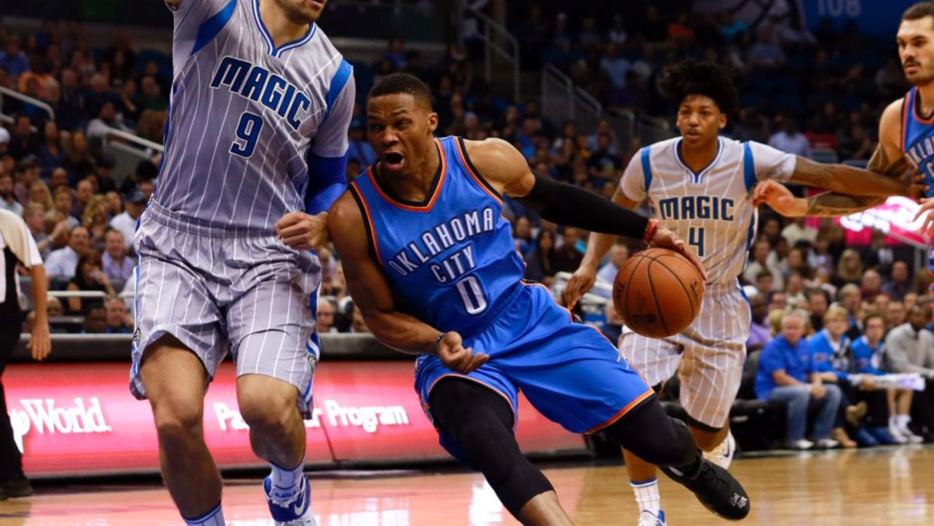 Oct 30, 2015; Orlando, FL, USA; Oklahoma City Thunder guard Russell Westbrook (0) drives to the basket as Orlando Magic center Nikola Vucevic (9) defends during the first quarter at Amway Center. Mandatory Credit: Kim Klement-USA TODAY Sports