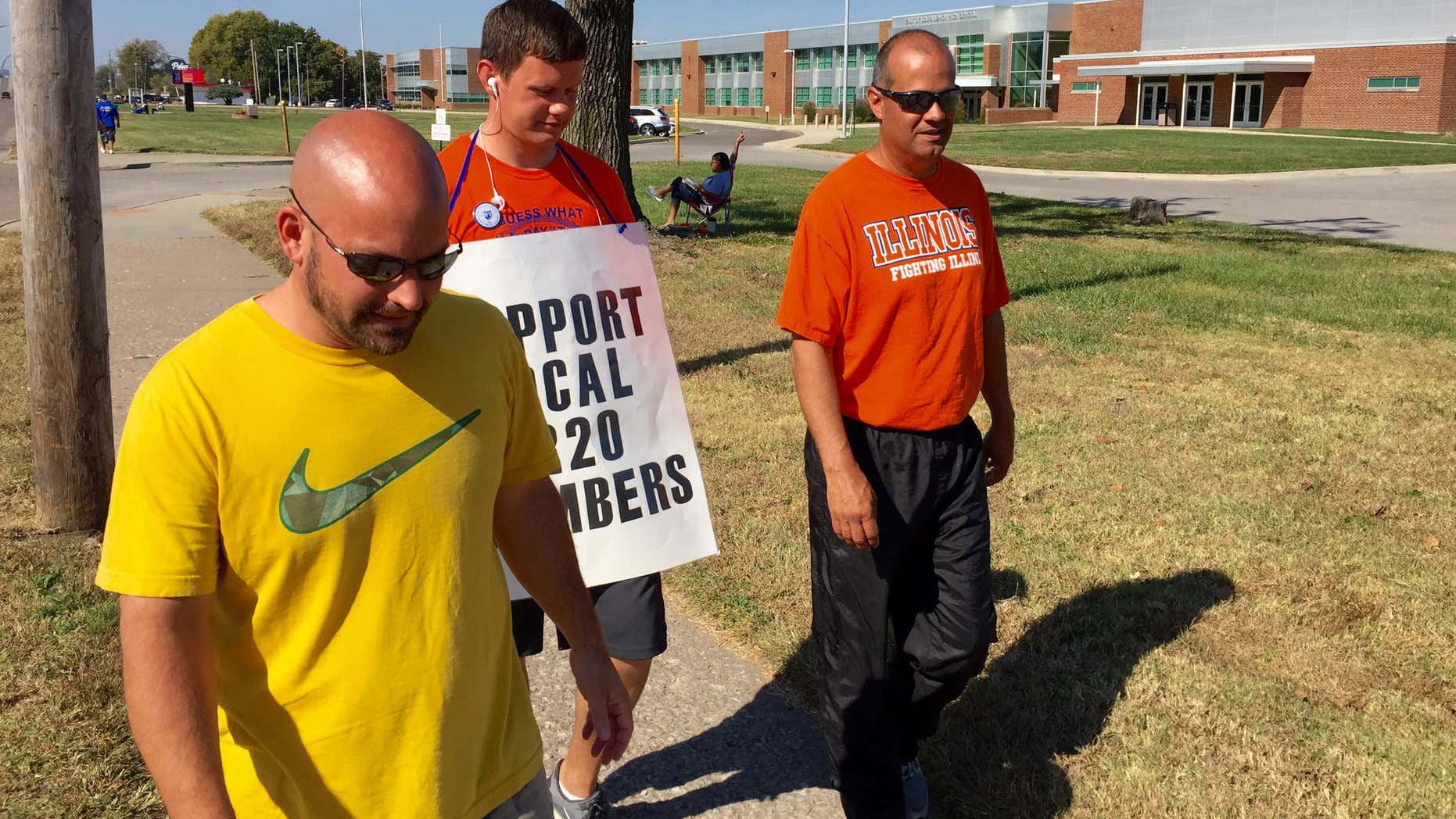 FILE - In this Oct. 27, 2015 file photo striking East St. Louis teachers, from left, Jeff Schneider, Josh Cummins and Paul Thies walk the picket line in front of East St. Louis Senior High School in East St. Louis, Ill.