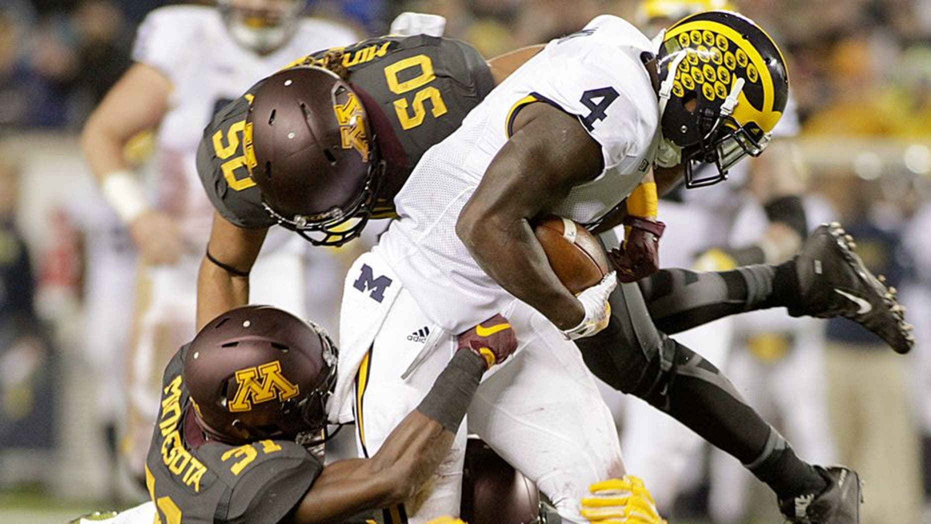 Michigan running back De'Veon Smith (4) is tackled by Minnesota's Eric Murray (31) and Jack Lynn (50) after a 15 yard catch and run during the first half of an NCAA college football game Saturday, Oct. 31, 2015, in Minneapolis.(AP Photo/Paul Battaglia)