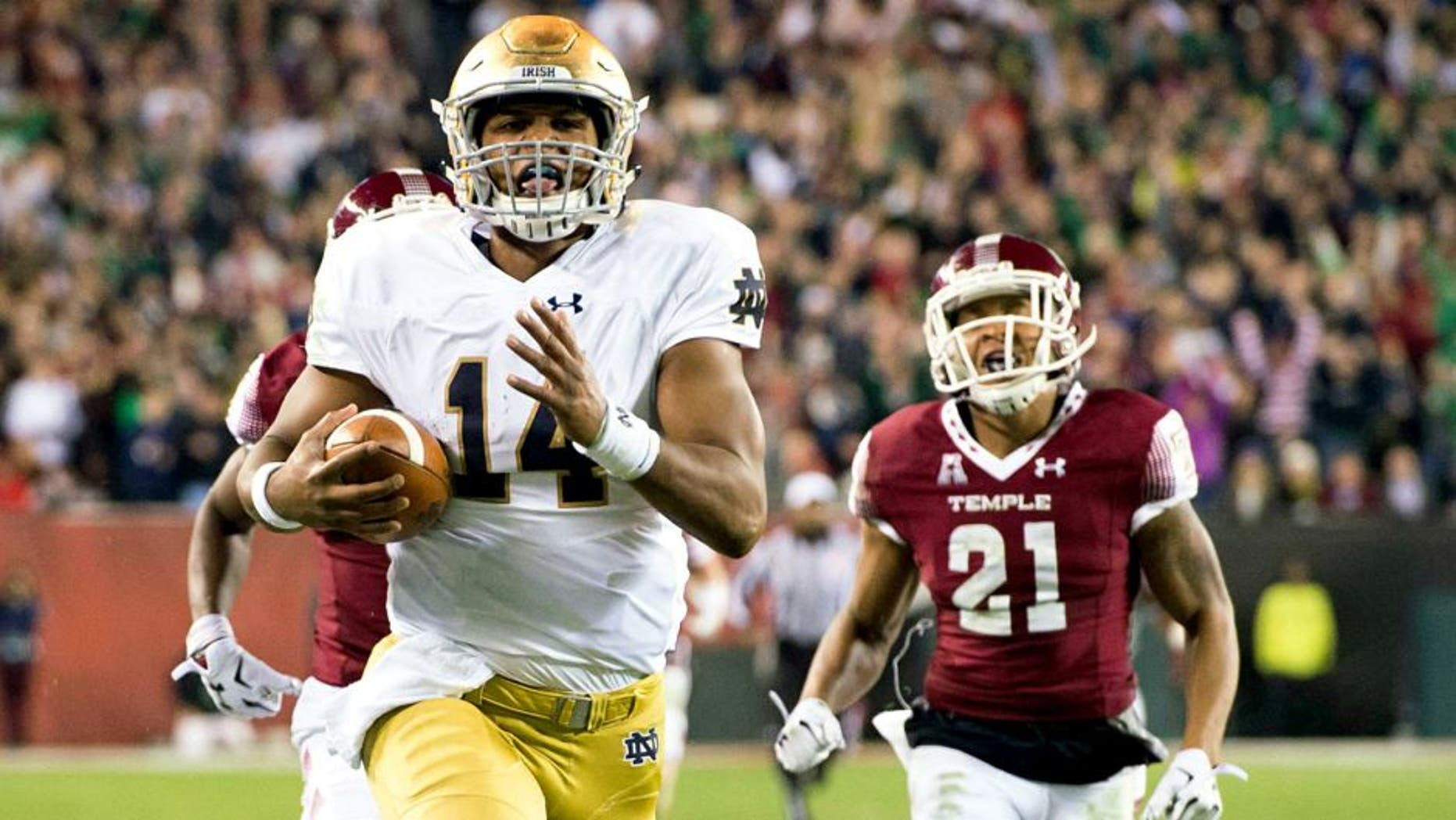 Oct 31, 2015; Philadelphia, PA, USA; Notre Dame Fighting Irish quarterback DeShone Kizer (14) runs for a touchdown as Temple Owls safety Alex Wells (21) pursues in the second quarter at Lincoln Financial Field. Mandatory Credit: Matt Cashore-USA TODAY Sports