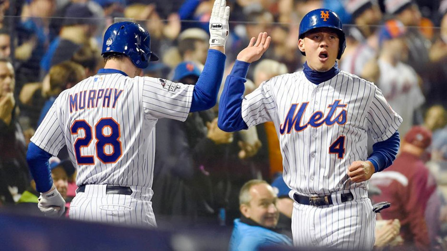 Oct 31, 2015; New York City, NY, USA; New York Mets shortstop Wilmer Flores (4) celebrates with second baseman Daniel Murphy (28) after scoring a run against the Kansas City Royals in the third inning in game four of the World Series at Citi Field. Mandatory Credit: Robert Deutsch-USA TODAY Sports