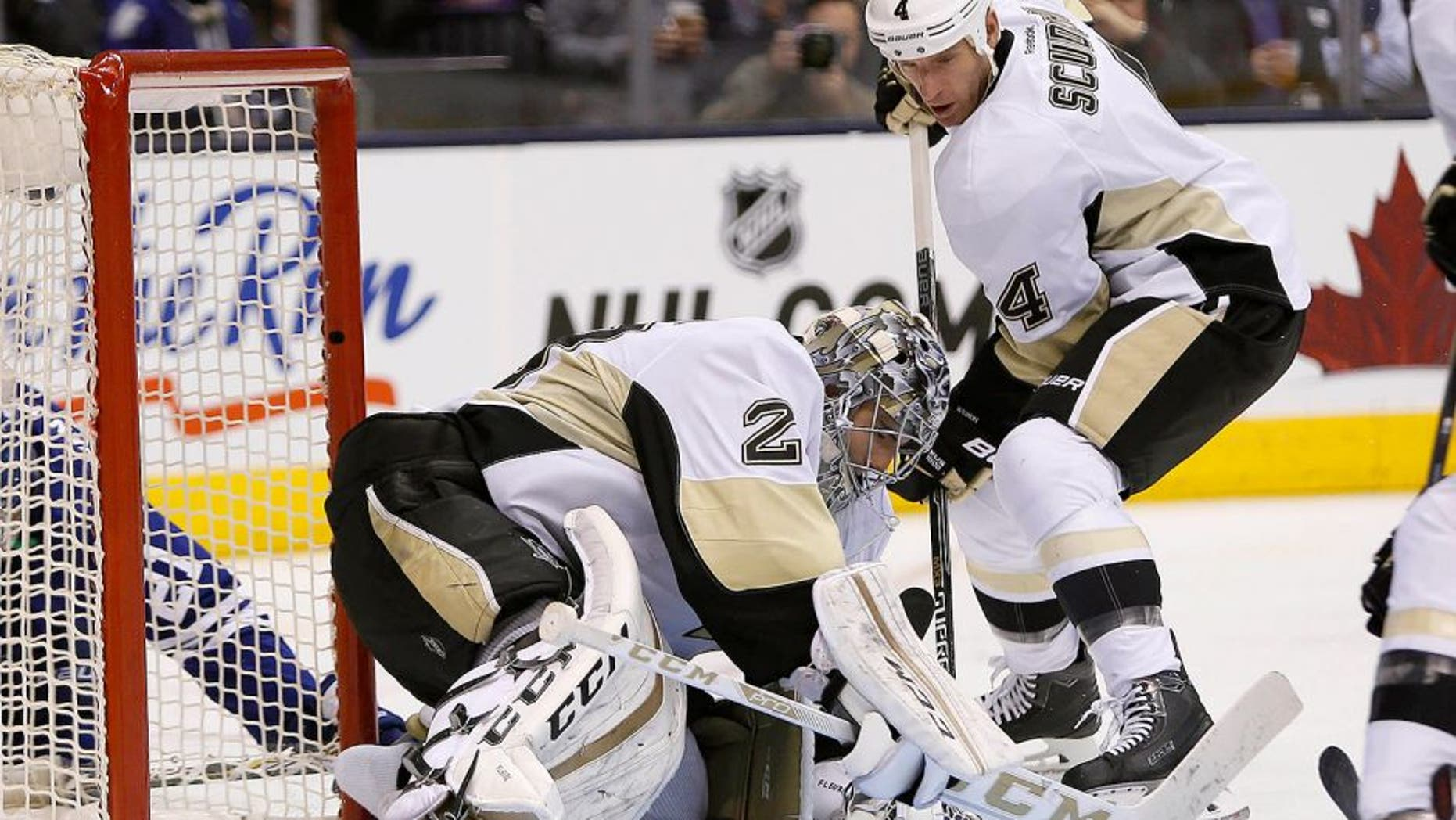 Oct 31, 2015; Toronto, Ontario, CAN; Pittsburgh Penguins defenseman Rob Scuderi (4) helps Pittsburgh Penguins goaltender Marc-Andre Fleury (29) cover a loose puck against the Toronto Maple Leafs during the second period at the Air Canada Centre. Mandatory Credit: John E. Sokolowski-USA TODAY Sports