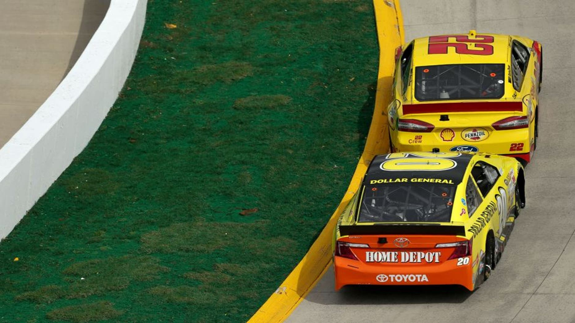 Joey Logano, driver of the #22 Shell-Pennzoil Ford, races with Matt Kenseth, driver of the #20 Dollar General Toyota, during the NASCAR Sprint Cup Series STP 500 at Martinsville Speedway on March 30, 2014 in Martinsville, Virginia.