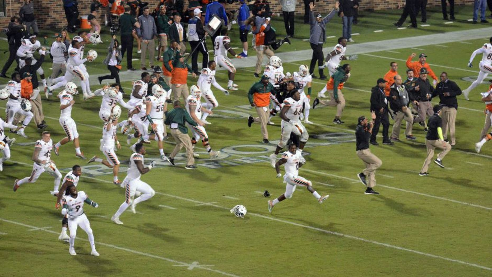 Miami players run onto the field to celebrate their 30-27 win over Duke in the final seconds of an NCAA college football game in Durham, N. C. (Bernard Thomas/The Herald-Sun via AP)