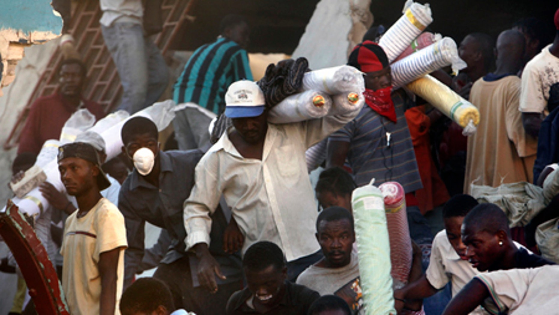 Jan. 16: People take goods from a collapsed store in Port-au-Prince.