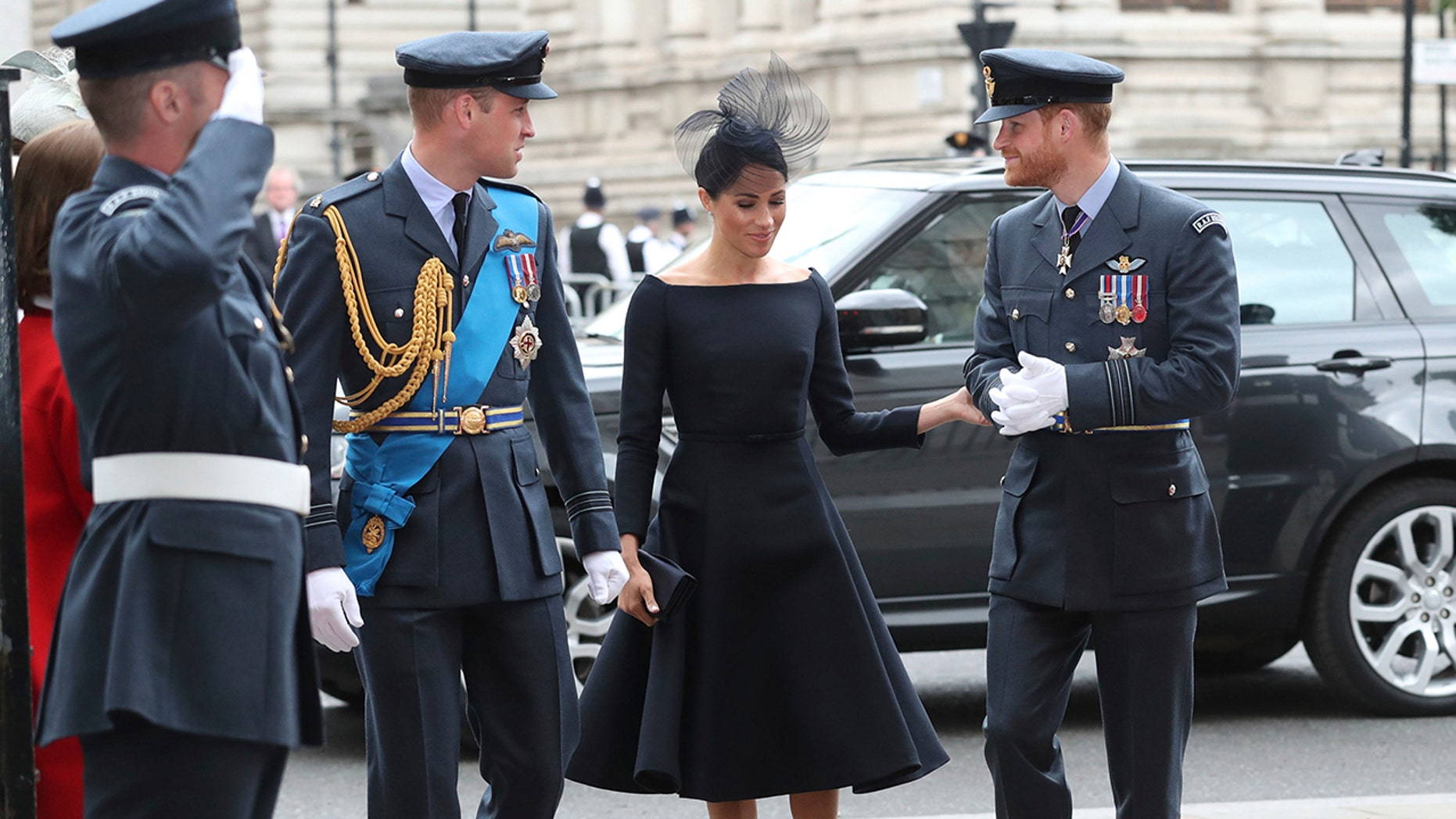 Meghan, the Duchess of Sussex, walks in with Prince Harry and Prince William as they arrive for a service at Westminster Abbey to mark the centenary of the Royal Air Force.