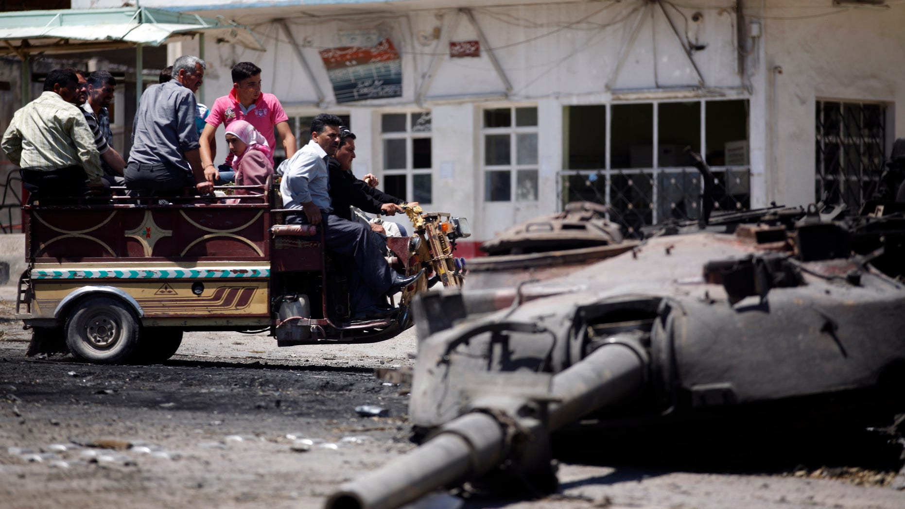June 10, 2012: Syrians look at a destroyed military tank at the northern town of Ariha, on the outskirts of Idlib, Syria.