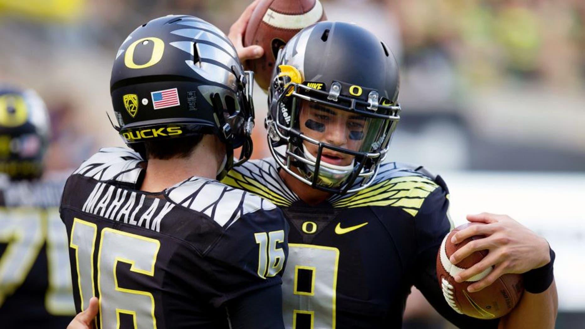 Nov 1, 2014; Eugene, OR, USA; Oregon Ducks quarterback Morgan Mahalak (16) and quarterback Marcus Mariota (8) talk before the game against the Stanford Cardinal at Autzen Stadium. Mandatory Credit: Scott Olmos-USA TODAY Sports