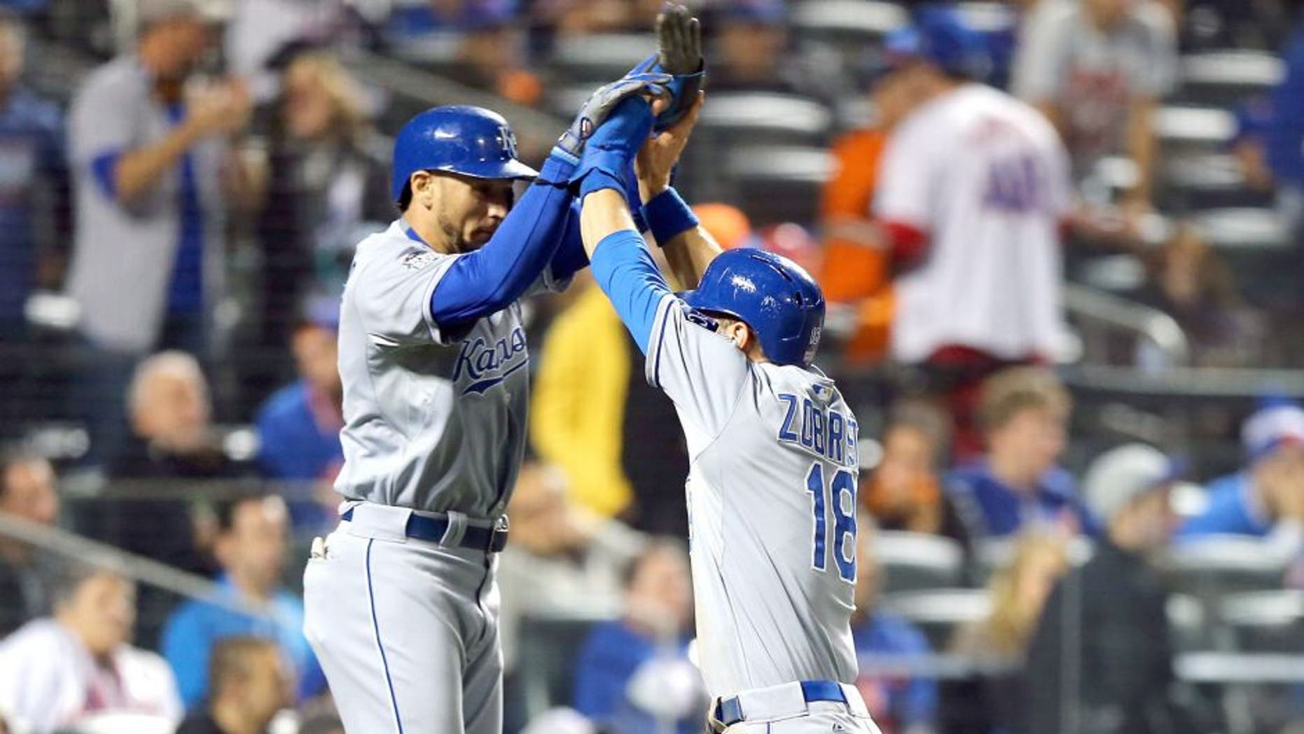 NEW YORK, NY - NOVEMBER 01: Ben Zobrist #18 of the Kansas City Royals celebrates with Christian Colon #16 and Alcides Escobar #2 after scoring off of a three run RBI double hit by Lorenzo Cain #6 in the twelfth inning against Bartolo Colon #40 of the New York Mets during Game Five of the 2015 World Series at Citi Field on November 1, 2015 in the Flushing neighborhood of the Queens borough of New York City. (Photo by Elsa/Getty Images)