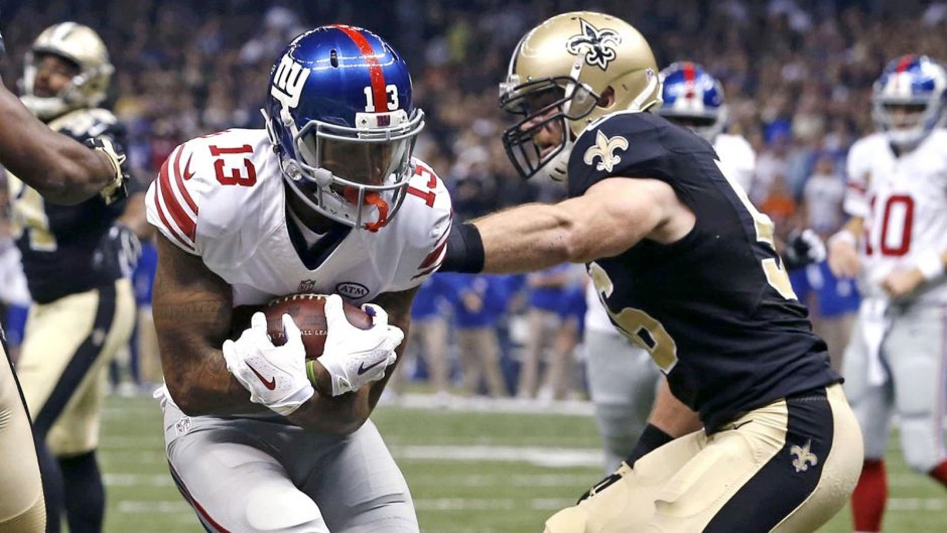 New York Giants wide receiver Odell Beckham (13) pulls in a touchdown reception in front of New Orleans Saints cornerback Delvin Breaux (40) in the first half of an NFL football game in New Orleans, Sunday, Nov. 1, 2015. (AP Photo/Jonathan Bachman)