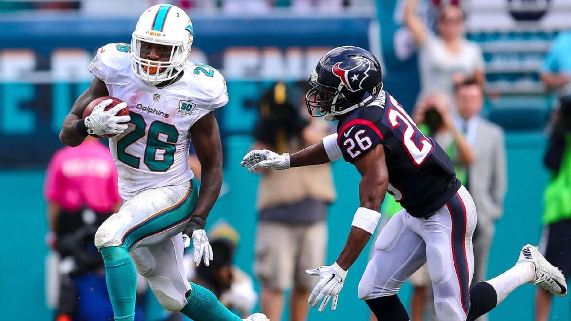 Oct 25, 2015; Miami Gardens, FL, USA; Miami Dolphins running back Lamar Miller (26) runs past Houston Texans defensive back Rahim Moore (26) during a game at Sun Life Stadium. Mandatory Credit: Steve Mitchell-USA TODAY Sports