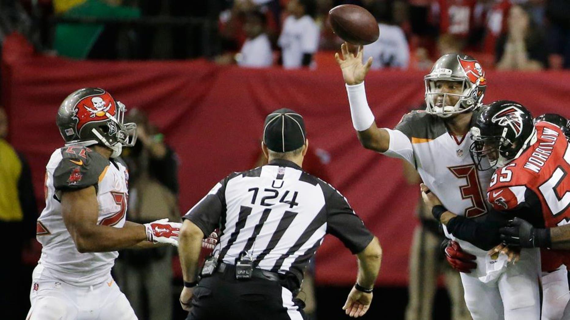 Tampa Bay Buccaneers quarterback Jameis Winston (3) makes the pass to Tampa Bay Buccaneers running back Doug Martin (22) as Atlanta Falcons middle linebacker Paul Worrilow (55) is hitting during the second of an NFL football game, Sunday, Nov. 1, 2015, in Atlanta. (AP Photo/David Goldman)