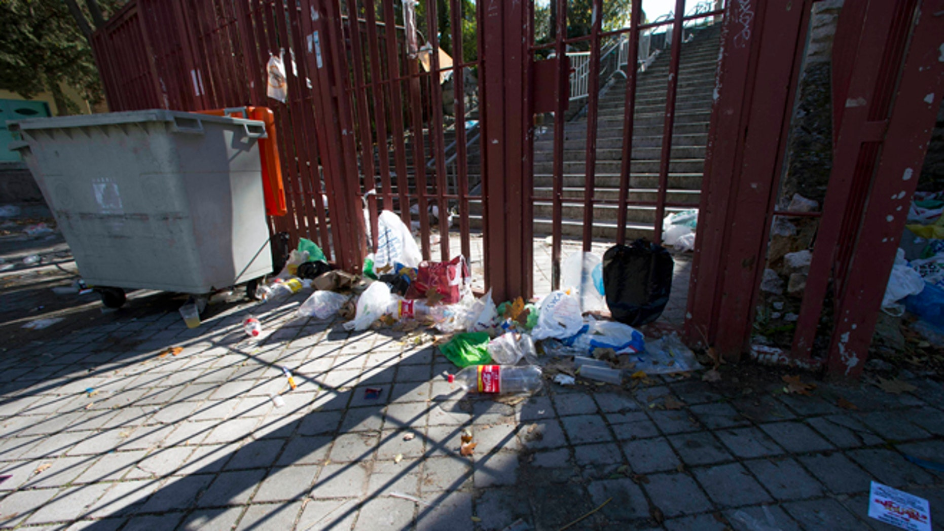 Nov. 1, 2012: Empty bottles and other debris lie outside the closed gates of the Madrid Arena venue in Madrid.