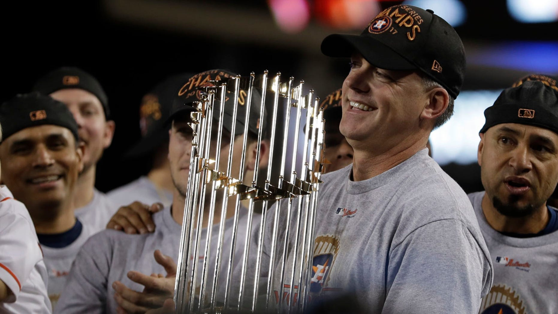Houston Astros manager A.J. Hinch holds the championship trophy after Game 7 of baseball's World Series against the Dodgers in Los Angeles, Nov. 1, 2017.