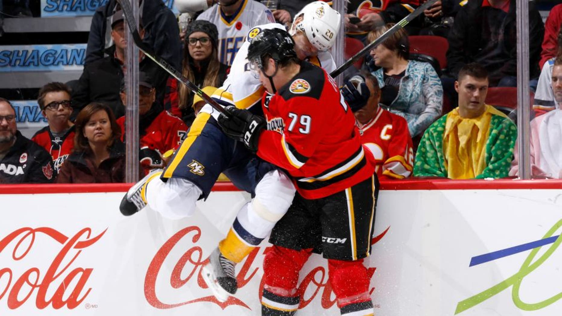 CALGARY, AB - OCTOBER 31: Michael Ferland #79 of the Calgary Flames checks Anton Volchenkov #20 of the Nashville Predators into the boards at Scotiabank Saddledome on October 31, 2014 in Calgary, Alberta, Canada. (Photo by Gerry Thomas/NHLI via Getty Images)