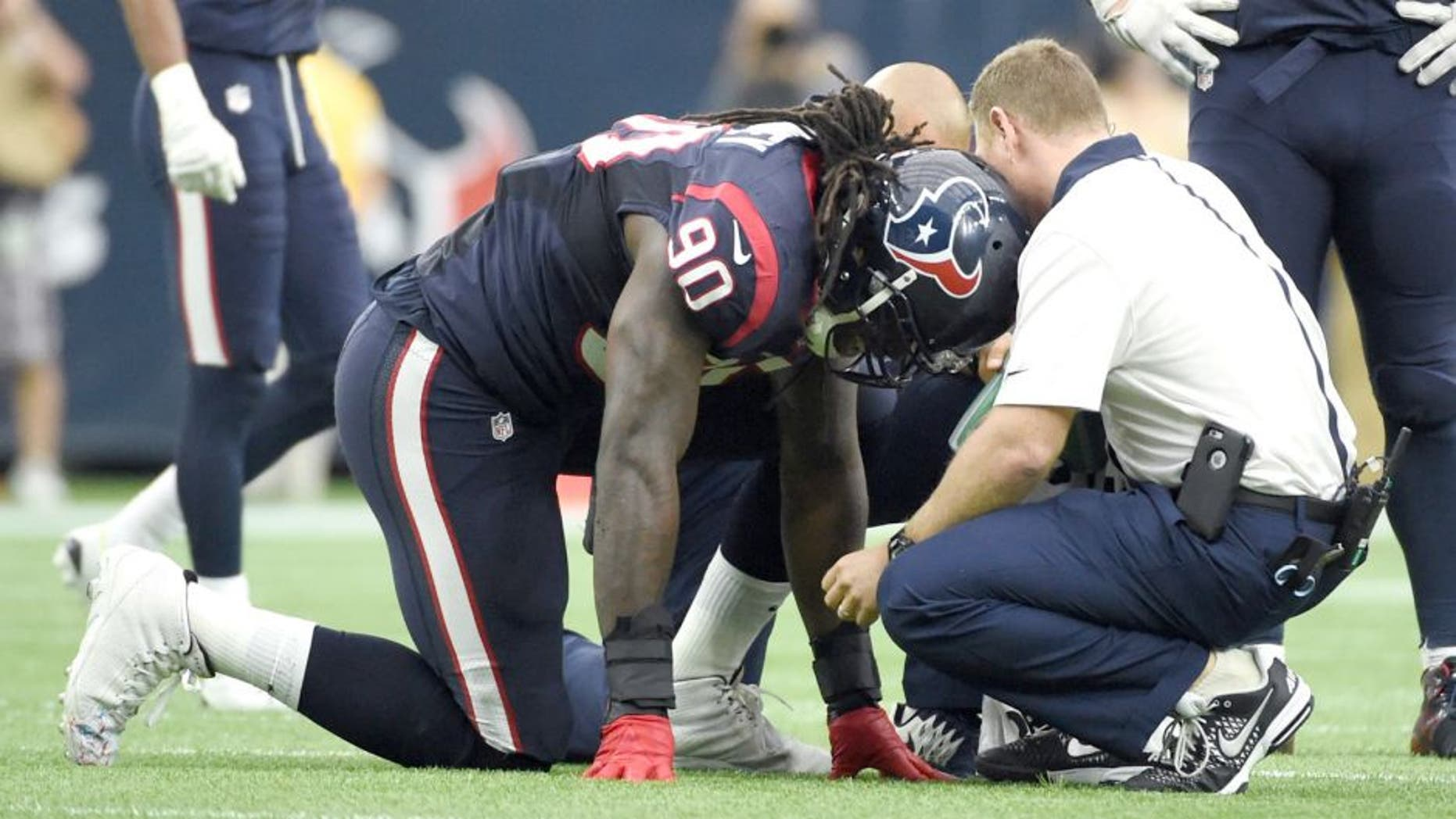 Houston Texans outside linebacker Jadeveon Clowney (90) is attended to after he was injured during the first half of an NFL football game against the Tennessee Titans, Sunday, Nov. 1, 2015, in Houston. (AP Photo/Eric Christian Smith)
