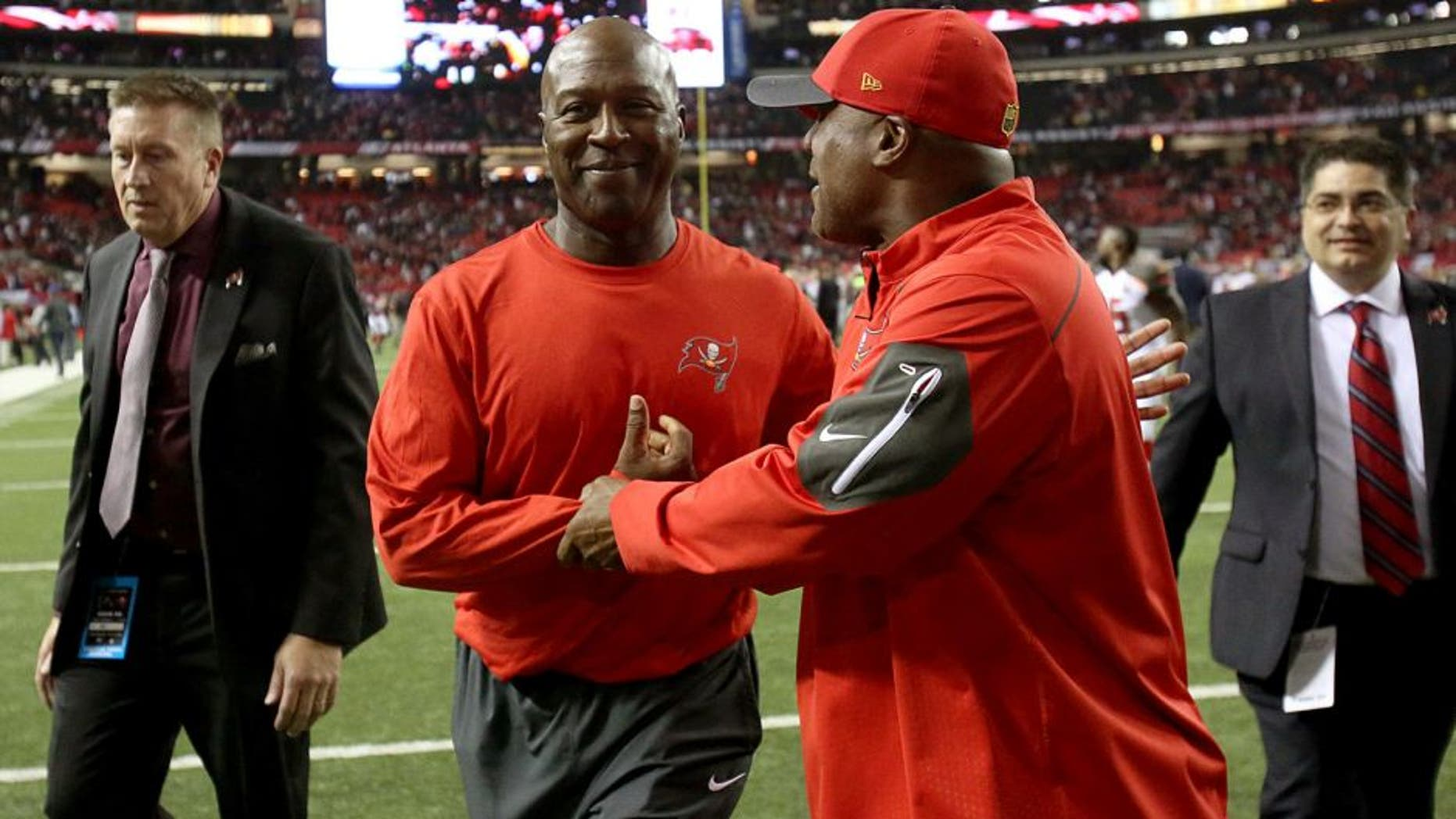 Nov 1, 2015; Atlanta, GA, USA; Tampa Bay Buccaneers head coach Lovie Smith, center, celebrates their win with cornerbacks coach Gill Byrd after their game against the Atlanta Falcons at the Georgia Dome. The Buccaneers won 23-20 in overtime. Mandatory Credit: Jason Getz-USA TODAY Sports