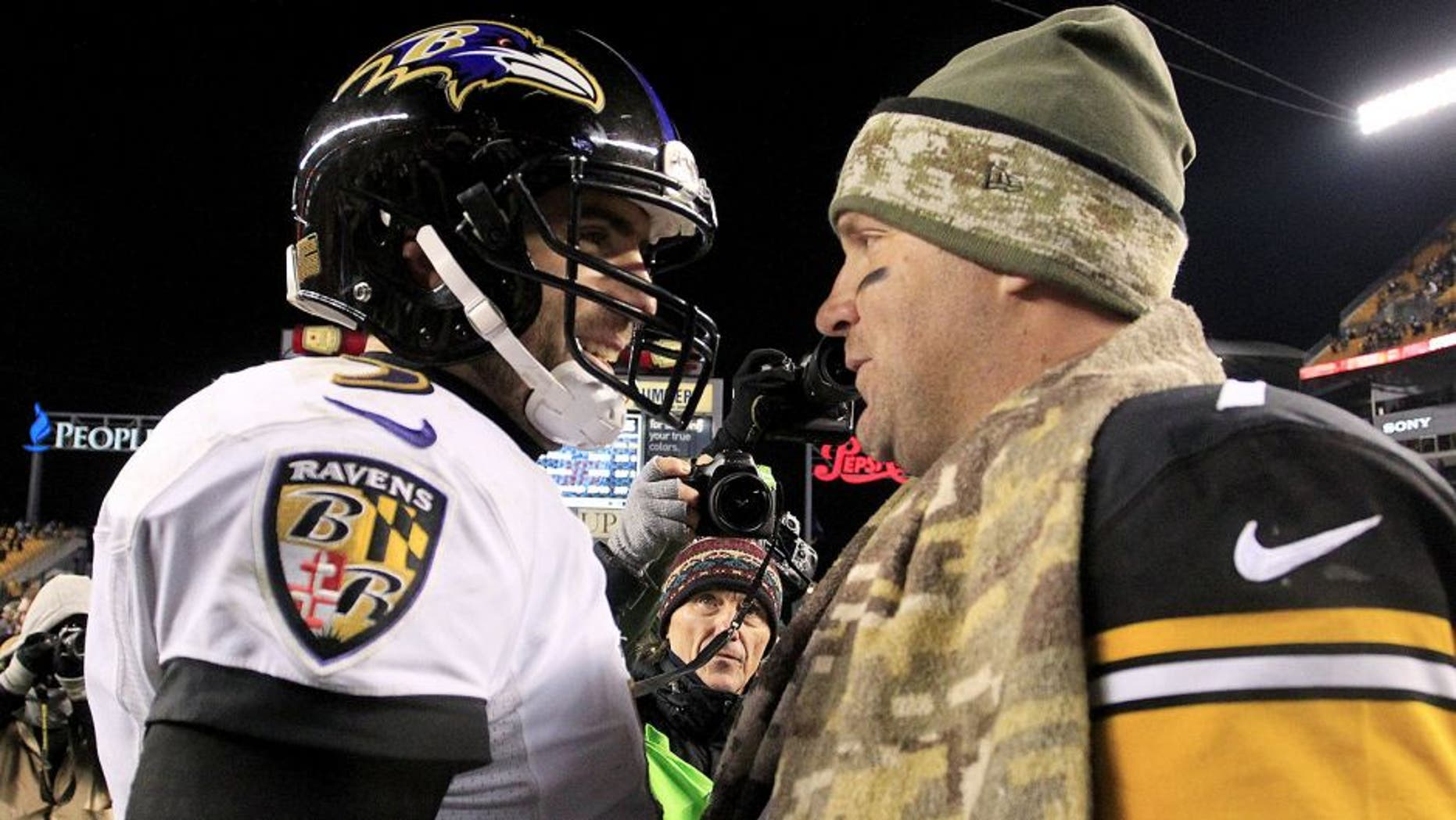 Nov 2, 2014; Pittsburgh, PA, USA; Baltimore Ravens quarterback Joe Flacco (left) and Pittsburgh Steelers quarterback Ben Roethlisberger (right) meet at mid-field after their game at Heinz Field. The Steelers won 43-23. Mandatory Credit: Charles LeClaire-USA TODAY Sports