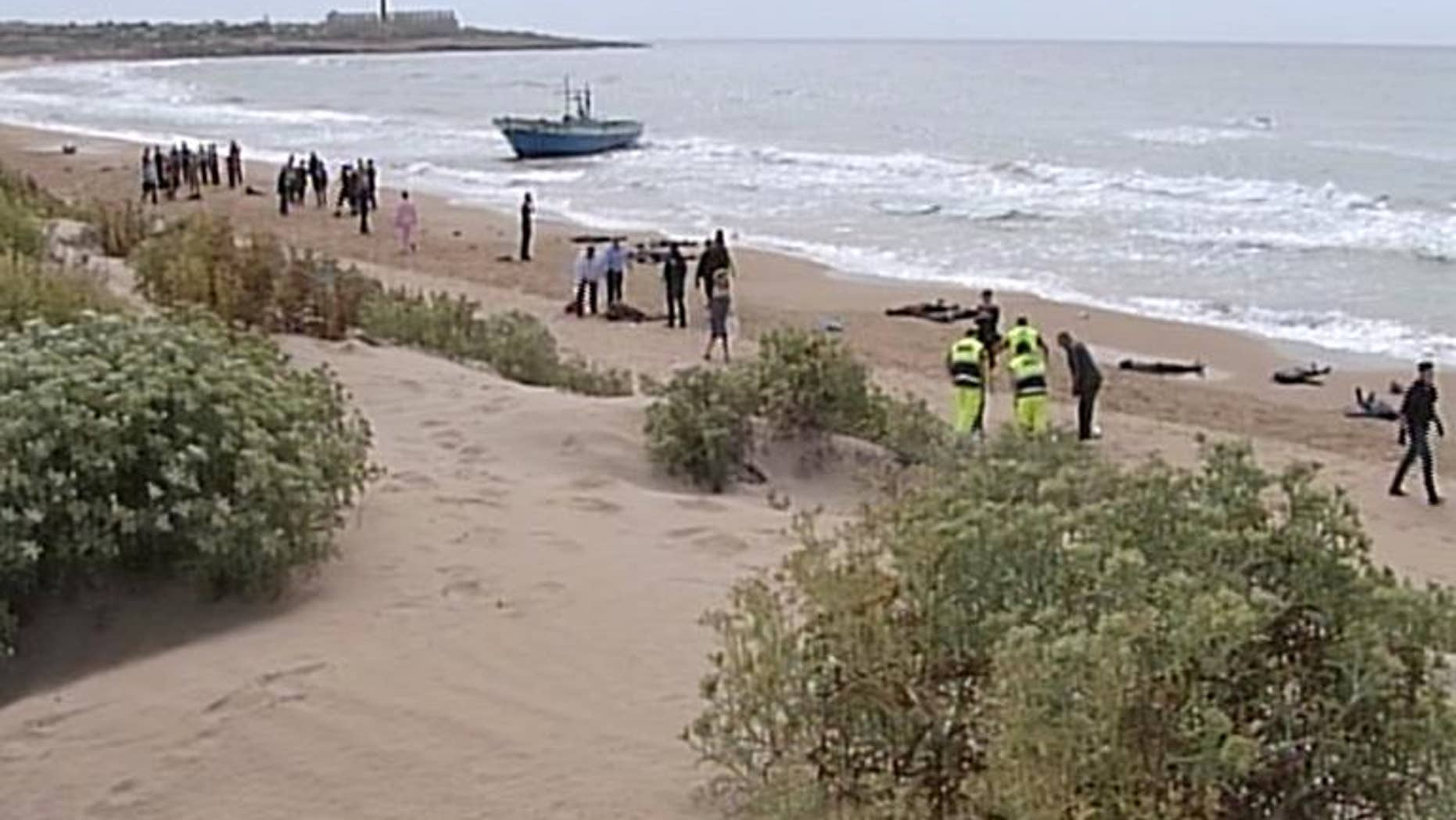 """A video grab released on September 30, 2013 by """"Video Mediterraneo"""" shows rescuers and policemen next to the bodies of migrants on the beach of Scicli"""