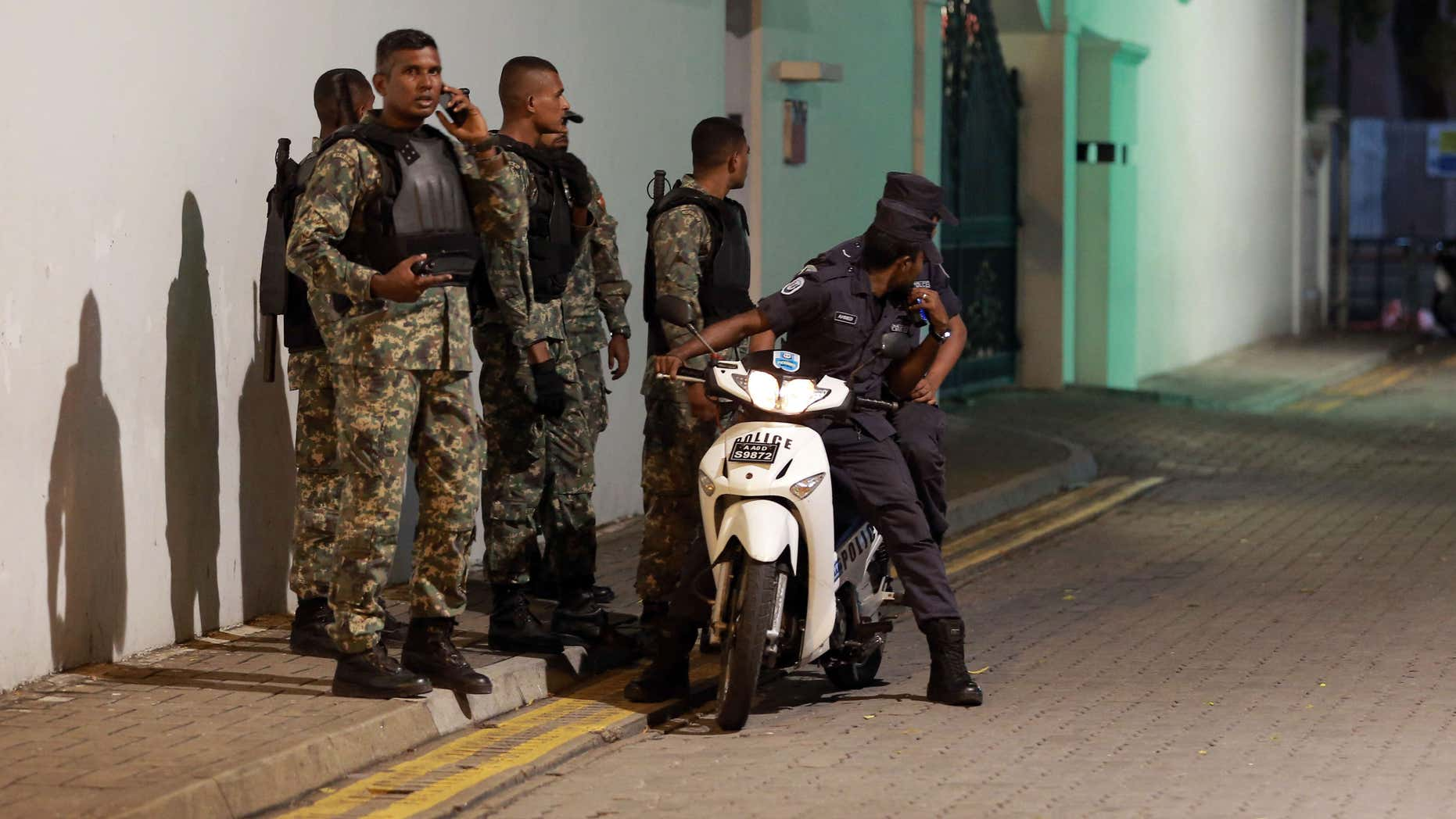 Nov. 2, 2015: Maldivian security officers stand guard near the president's official residence where the military found and deactivated an explosive device in Male, Maldives.