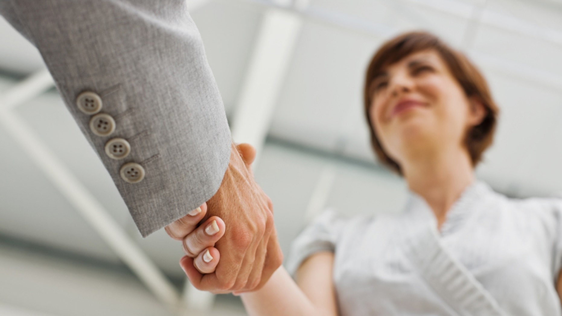 Closeup of human hands shaking hands in office