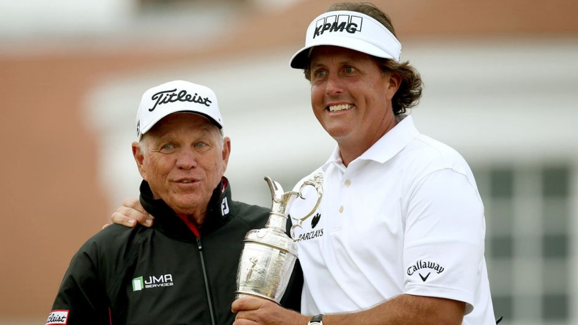 US golfer Phil Mickelson poses for pictures with his coach Butch Harmon and his trophy the Claret Jug after winning the 2013 British Open Golf Championship at Muirfield golf course at Gullane in Scotland on July 21, 2013. Mickelson won the British Open at Muirfield with a superb final round of 66. The 43-year-old American won with a three under total of 281, three strokes clear of Henrik Stenson who had a closing 70.AFP PHOTO/ADRIAN DENNIS (Photo credit should read ADRIAN DENNIS/AFP/Getty Images)