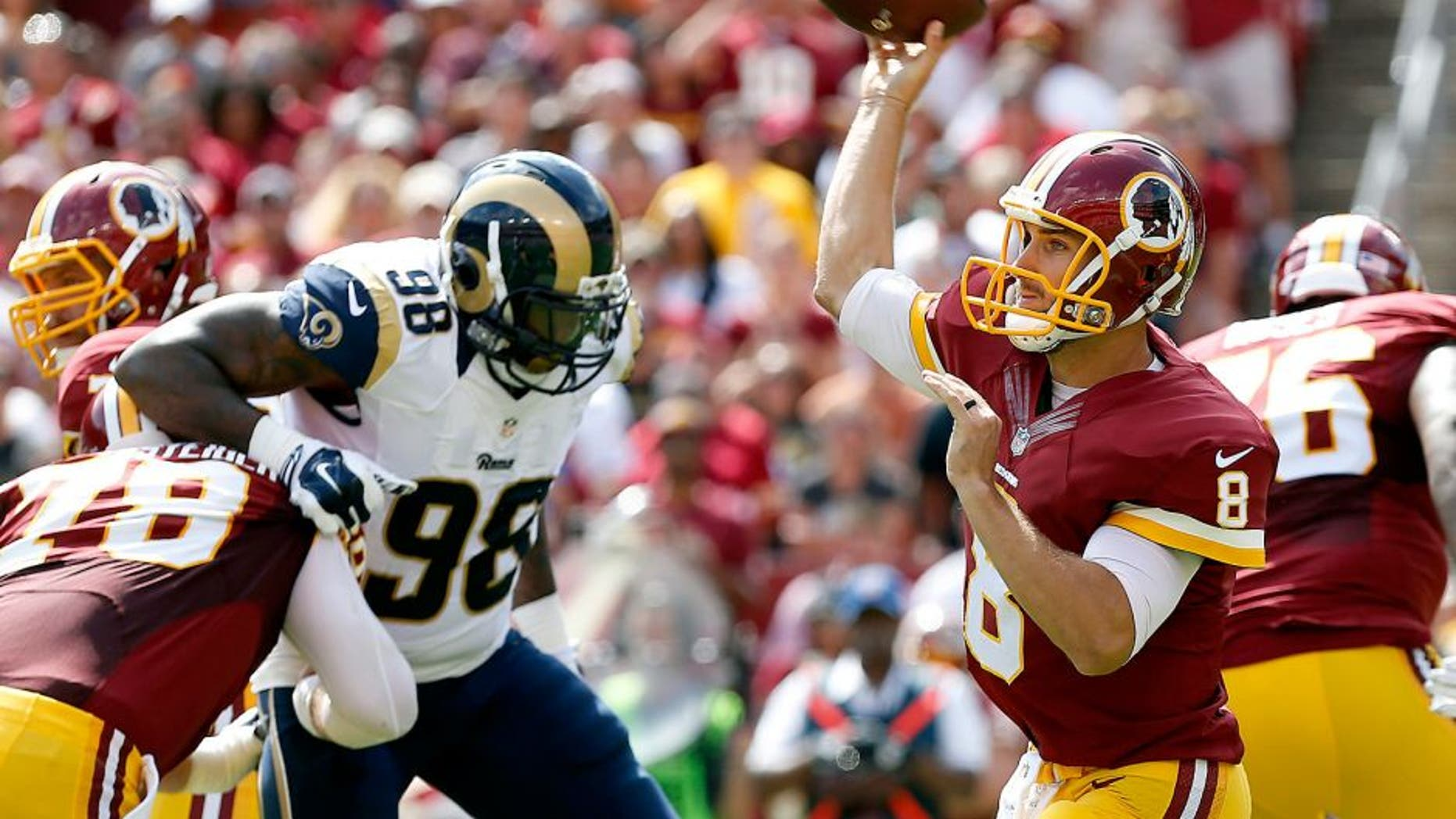 Sep 20, 2015; Landover, MD, USA; Washington Redskins quarterback Kirk Cousins (8) throws the ball as St. Louis Rams defensive tackle Nick Fairley (98) chases in the first quarter at FedEx Field. Mandatory Credit: Geoff Burke-USA TODAY Sports