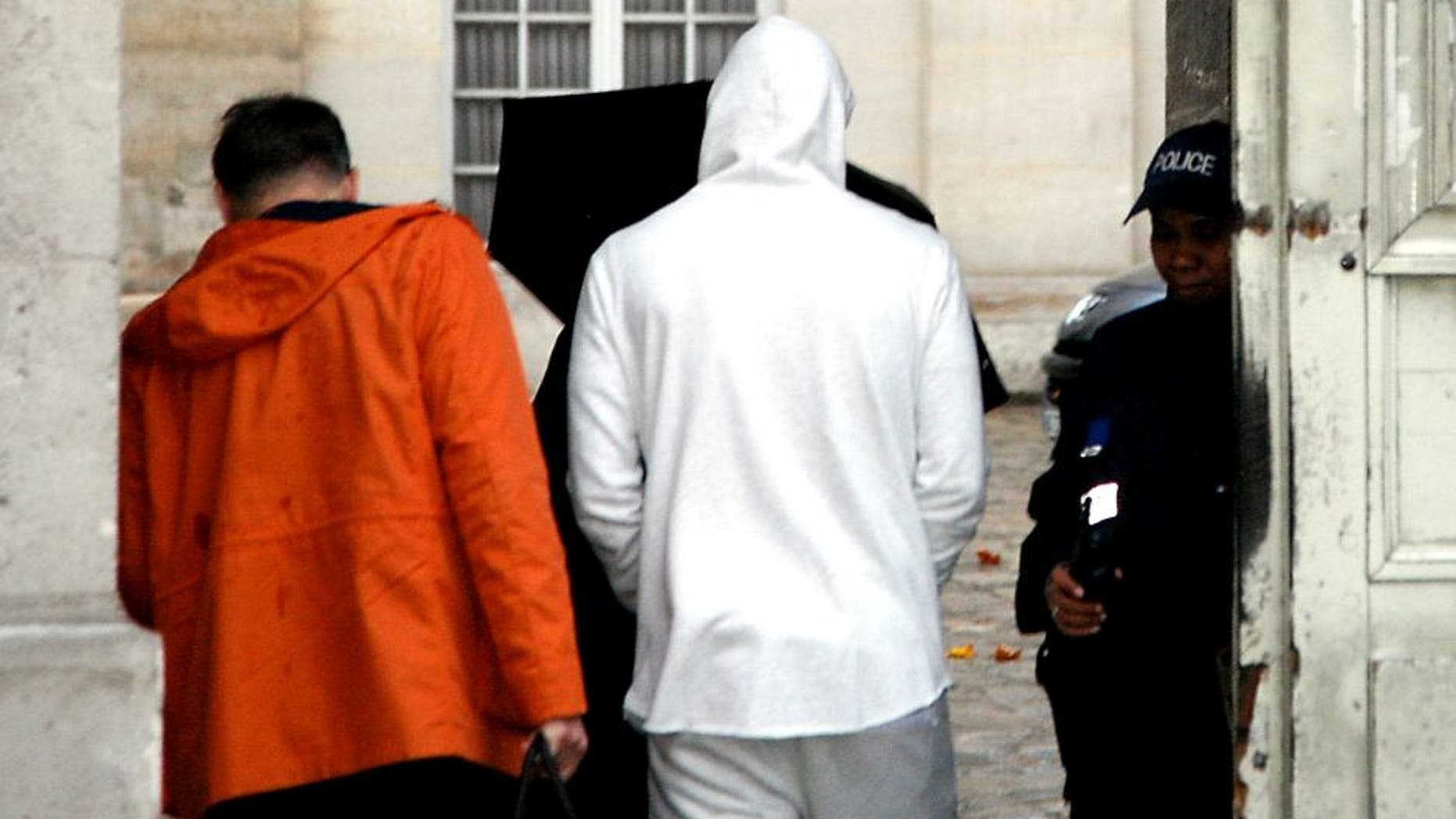 French footballer Karim Benzema (C), wearing a white hooded jersey, arrives at the police station in Versailles, southwest of Paris, on November 4, 2015. French footballer Karim Benzema was arrested on November 4 in connection with blackmail over a sextape featuring fellow player Mathieu Valbuena, a source close to the probe told AFP. AFP PHOTO / MATTHIEU ALEXANDRE (Photo credit should read MATTHIEU ALEXANDRE/AFP/Getty Images)