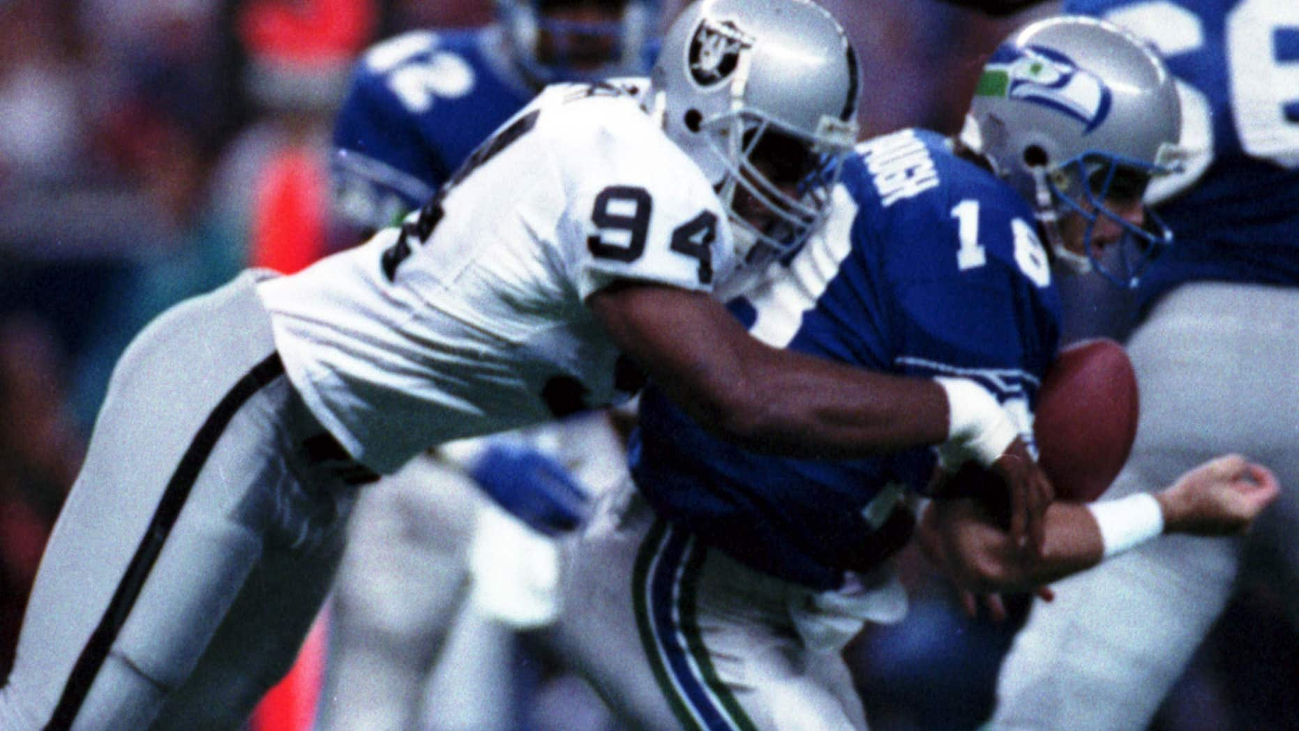 FILE - In this Oct. 18, 1992, file photo, Los Angeles Raiders' Anthony Smith (94) sacks Seattle Seahawks quarterback Stan Gelbaugh during the second quarter of an NFL football game in Seattle.