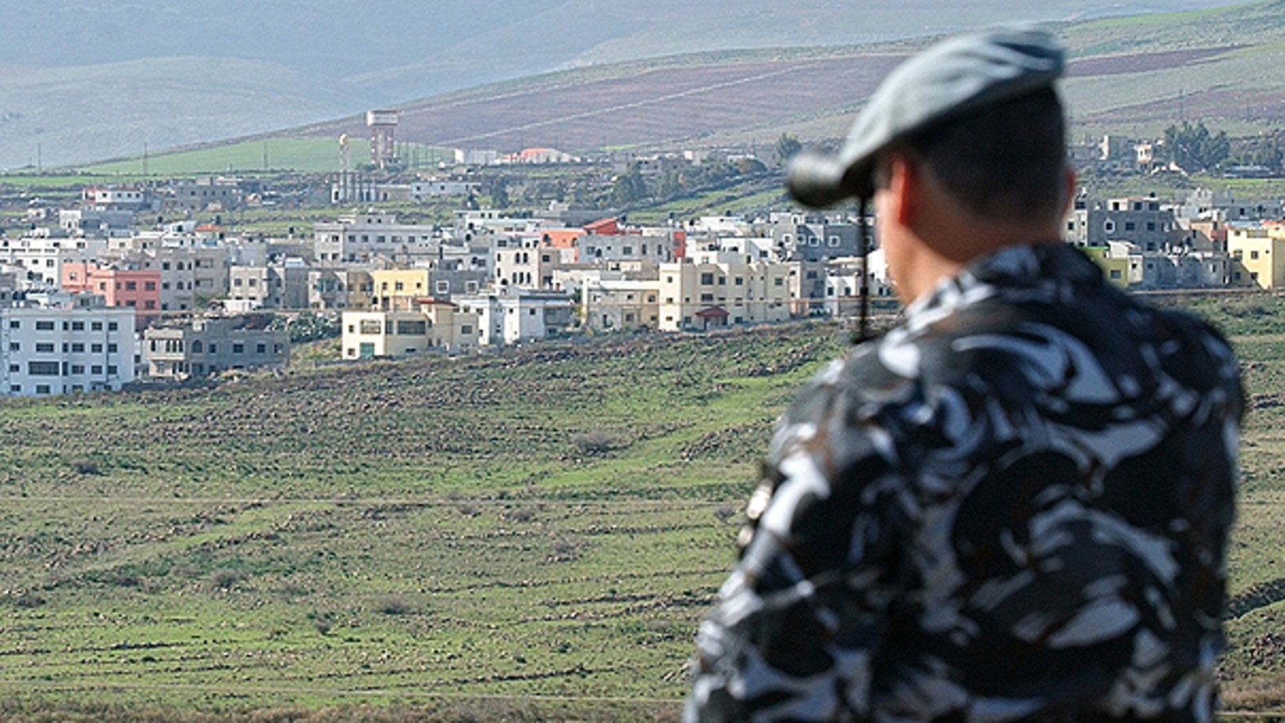 In this file photo taken on Jan. 3, 2006, a Lebanese security officer looks through binoculars at the Israeli part of the border village of Ghajar from the southern Lebanese village of Abbassiyeh in Lebanon.