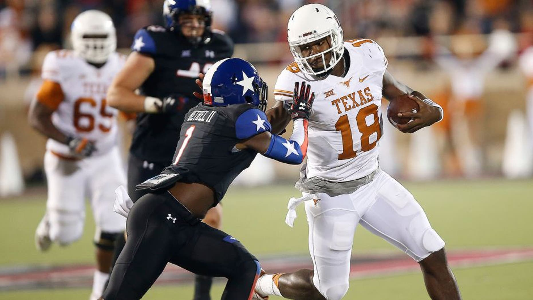 Texas' Tyrone Swoopes runs against Texas Tech's Nigel Bethel II during an NCAA college football game in Lubbock, Texas, Saturday, Nov. 1, 2014. (AP Photo/Lubbock Avalanche-Journal, Tori Eichberger)