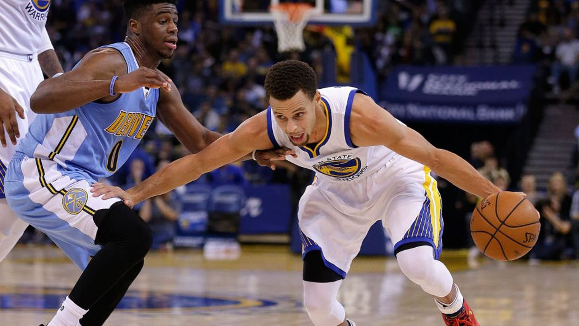 Golden State Warriors' Stephen Curry, right, drives the ball against Denver Nuggets' Emmanuel Mudiay during the second half of an NBA basketball game Friday, Nov. 6, 2015, in Oakland, Calif. (AP Photo/Ben Margot)
