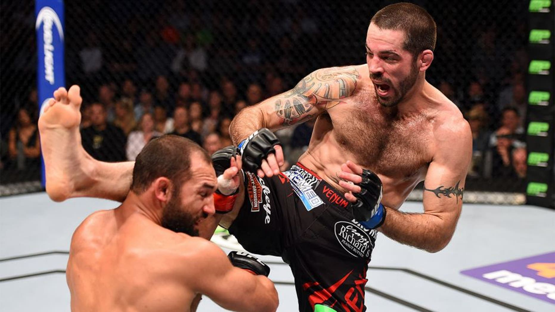 DALLAS, TX - MARCH 14: (R-L) Matt Brown kicks Johny Hendricks in their welterweight bout during the UFC 185 event at the American Airlines Center on March 14, 2015 in Dallas, Texas. (Photo by Josh Hedges/Zuffa LLC/Zuffa LLC via Getty Images)